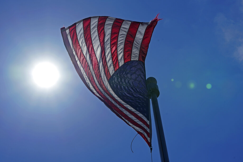 In this Wednesday, June 30, 2021 photo, a U.S. flag flies with the sun in the background in downtown Seattle. (AP Photo/Ted S. Warren, File)