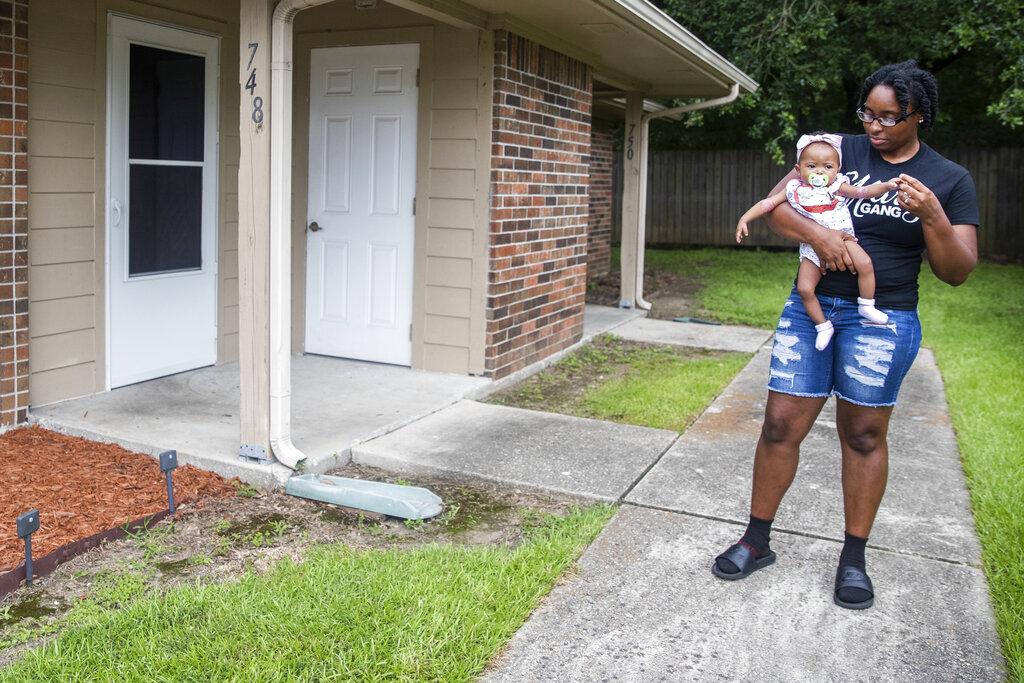 Tyesha Young, who lost her hospital job during the pandemic, holds her baby Jalayah Johnson outside their home in Waggaman, La., Friday, July 2, 2021. (AP Photo/Sophia Germer)