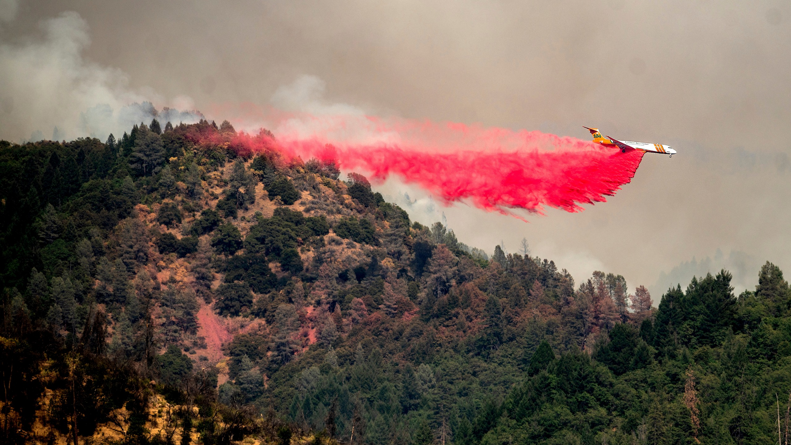 An air tanker drops retardant while trying to stop the Salt Fire from spreading near Lakehead in unincorporated Shasta County, Calif., on July 2, 2021. (Noah Berger / Associated Press)