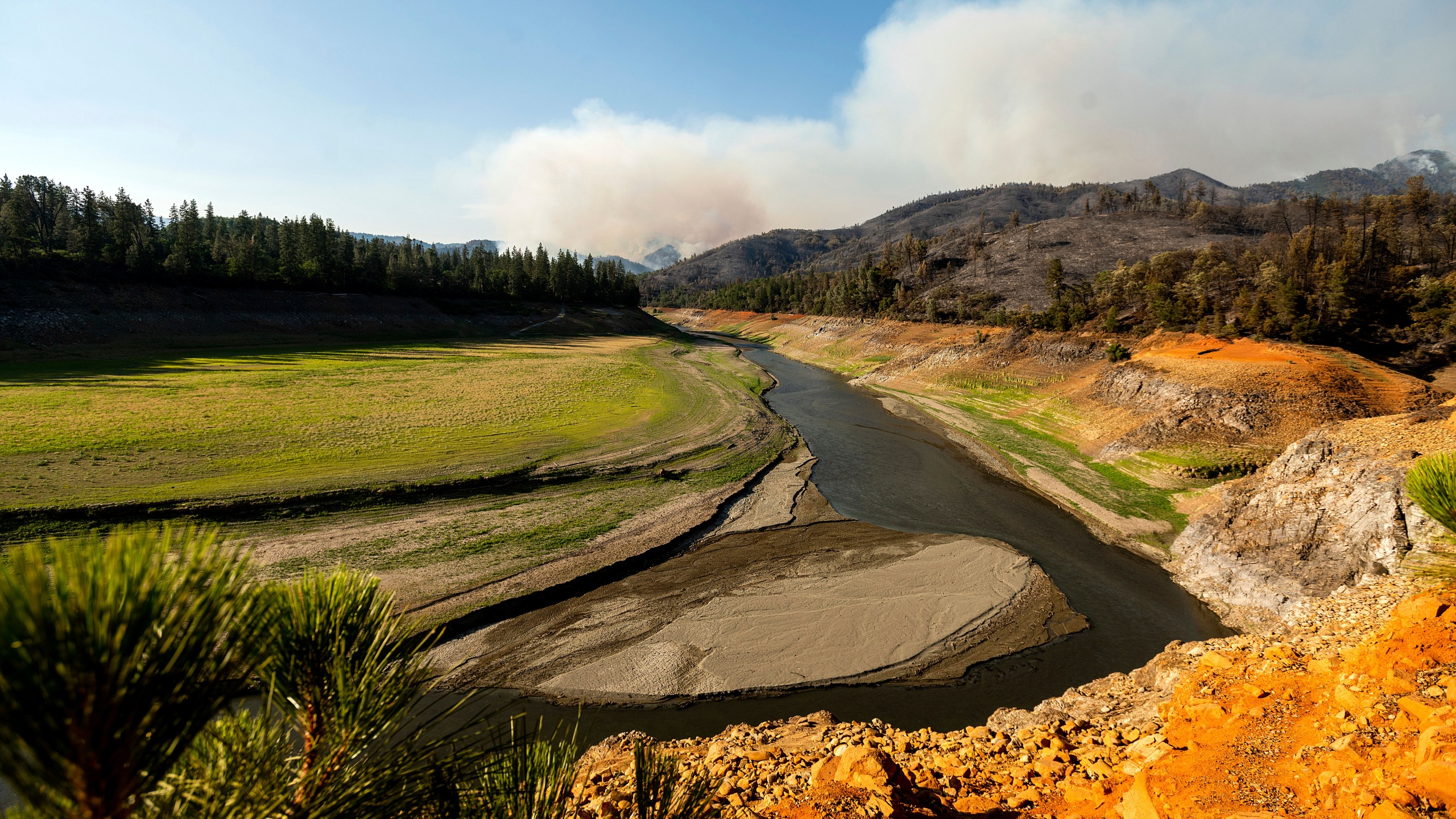 Smoke from the Salt Fire rises above Lake Shasta, which was at 38 percent of capacity at the time of this photo, on Friday, July 2, 2021, in unincorporated Shasta County, Calif. (AP Photo/Noah Berger)