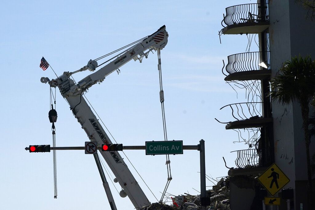 An American flag flies from a crane next to the Champlain Towers South condo building, where scores of victims remain missing more than a week after it partially collapsed, Sunday, July 4, 2021, in Surfside, Fla. (AP Photo/Lynne Sladky)