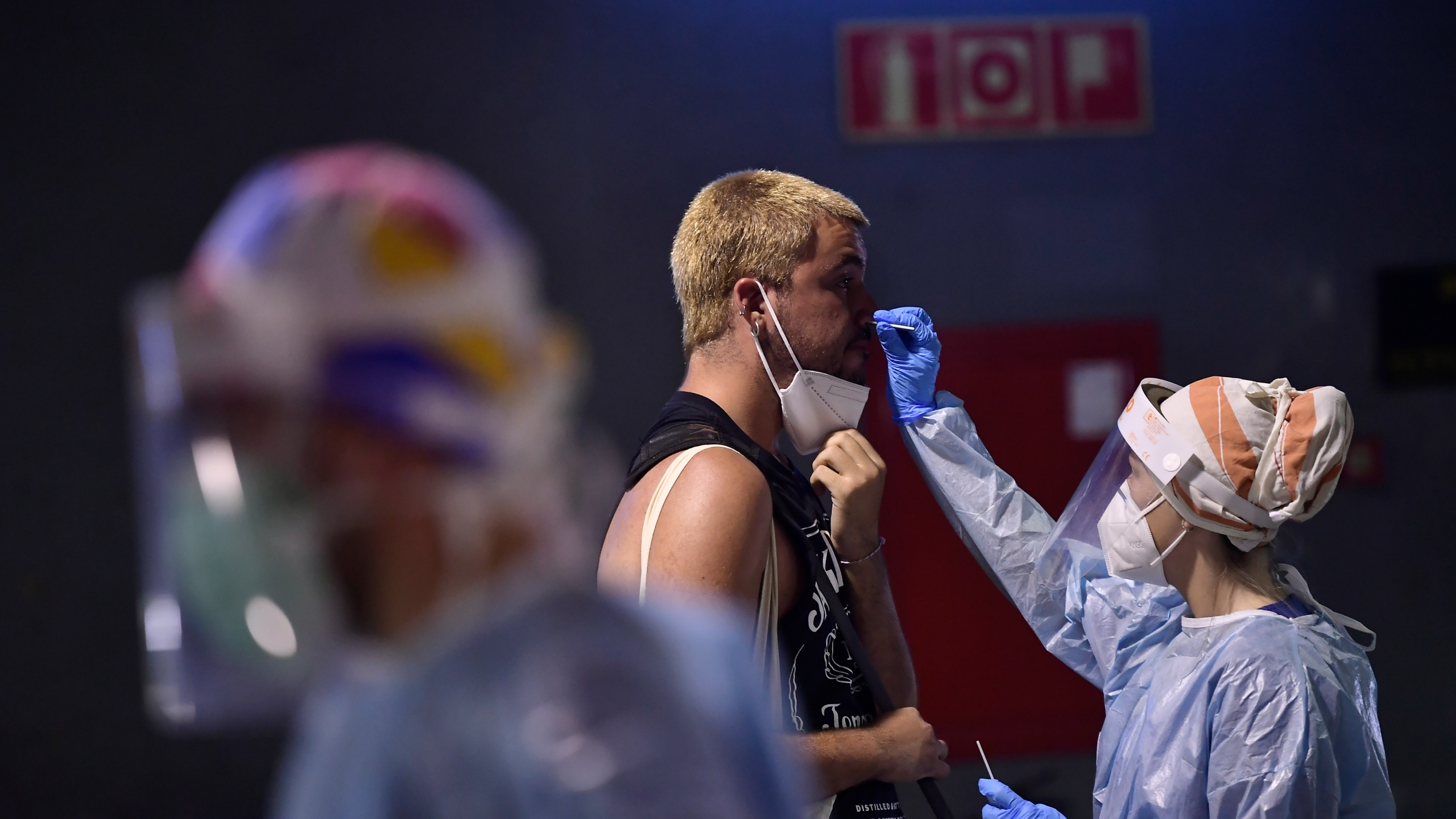 A health worker takes a swab from a teenager during a rapid antigen test for COVID-19 at bus station in Pamplona, northern Spain, on July 4, 2021. (Alvaro Barrientos / Associated Press)