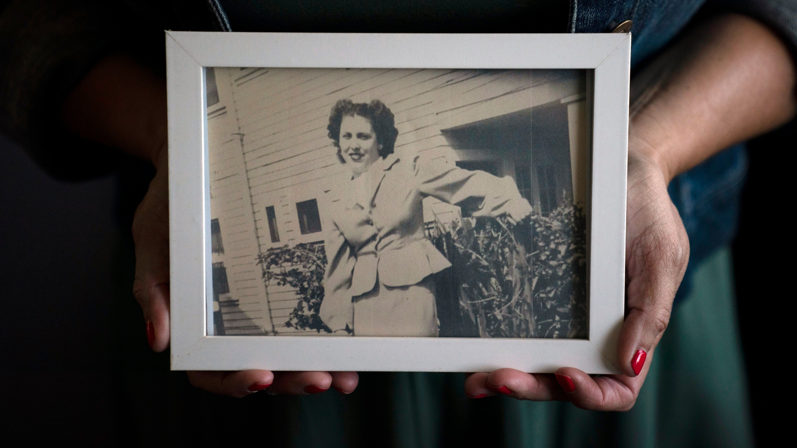 Stacy Cordova, whose aunt was a victim of California's forced sterilization program that began in 1909, holds a framed photo of her aunt Mary Franco on July 5, 2021, in Azusa. (Jae C. Hong / Associated Press)