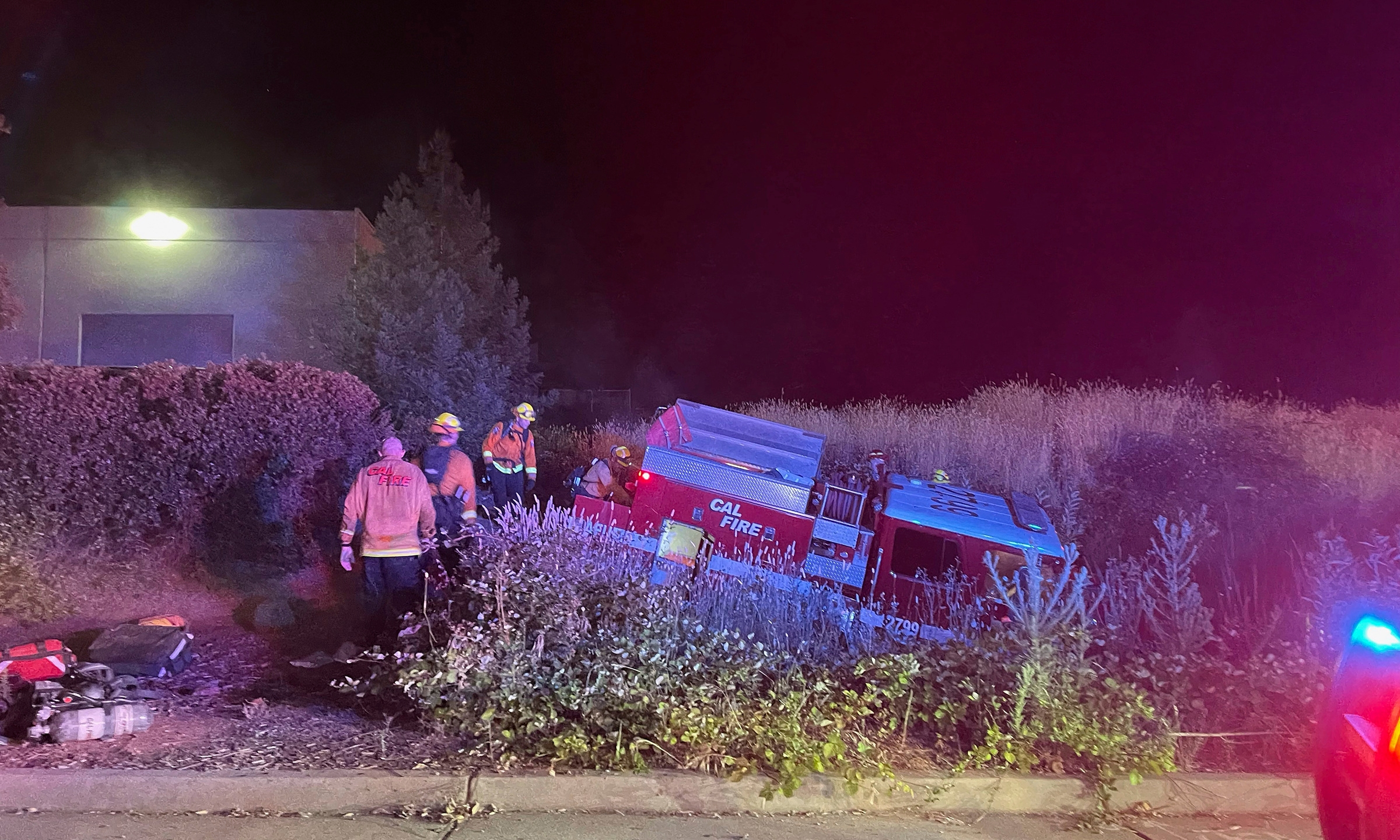In this photo provided by Bill Wilde, firefighters look over a California Department of Forestry and Fire Protection truck that crashed into a ditch after it was stolen by a California inmate on July 4, 2021, in Shingle Springs, Calif. (Bill Wilde Photo via AP)