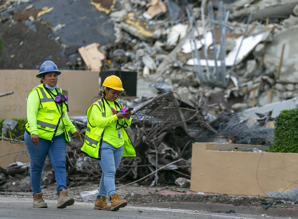A workers make her way past the rubble and debris of the Champlain Towers South condo in Surfside, Florida on Tuesday, July 6, 2021. (Matias J. Ocner/Miami Herald via AP)