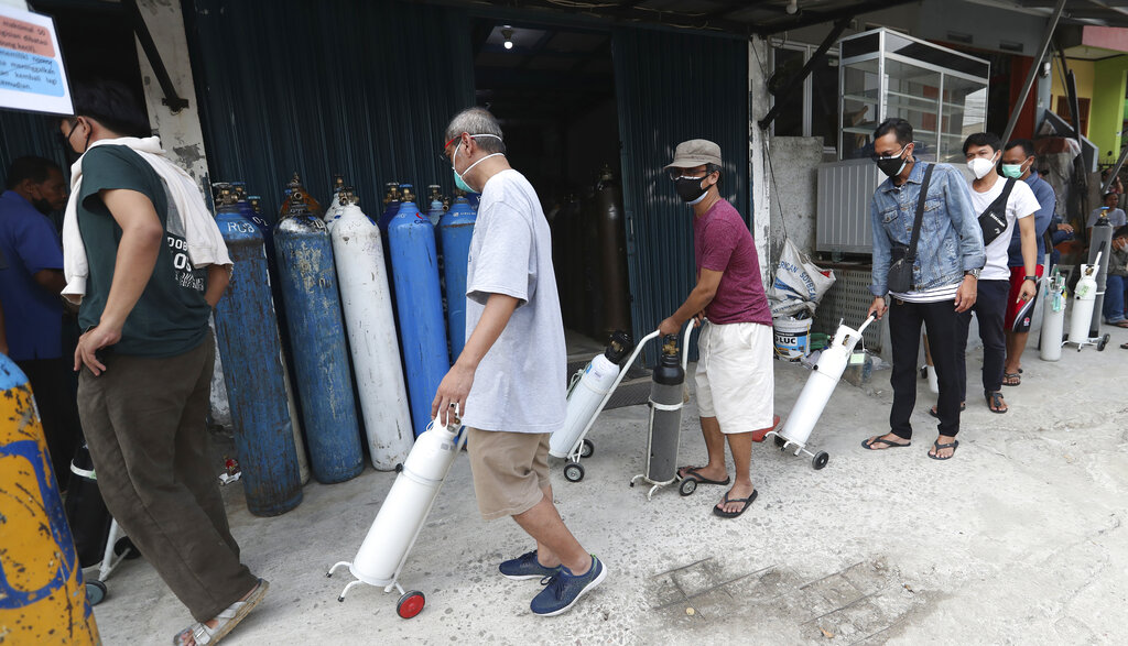 People line up to refill their oxygen tanks at a filling station in Jakarta, Indonesia, Wednesday, July 7, 2021. (AP Photo/Achmad Ibrahim)