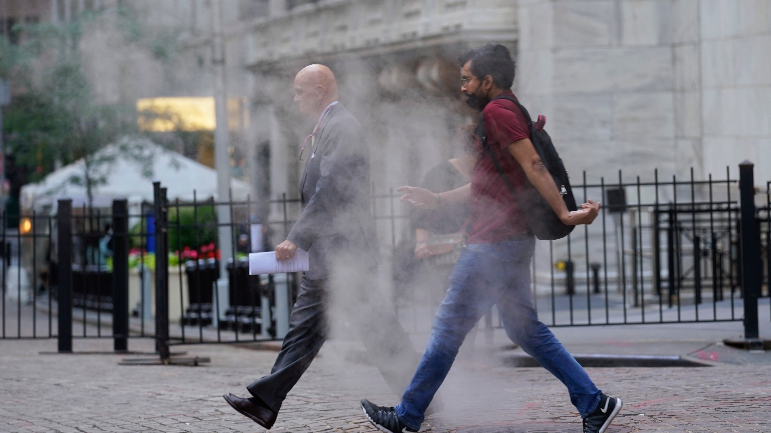 In this June 16, 2021 file photo, people walk through steam from a street grating during the morning commute in New York. Companies around the U.S. are scrambling to figure out how to bring employees back to the office after more than a year of them working remotely. Most are proceeding cautiously, trying to navigate declining COVID-19 infections against a potential backlash by workers who are not ready to return. (AP Photo/Richard Drew)