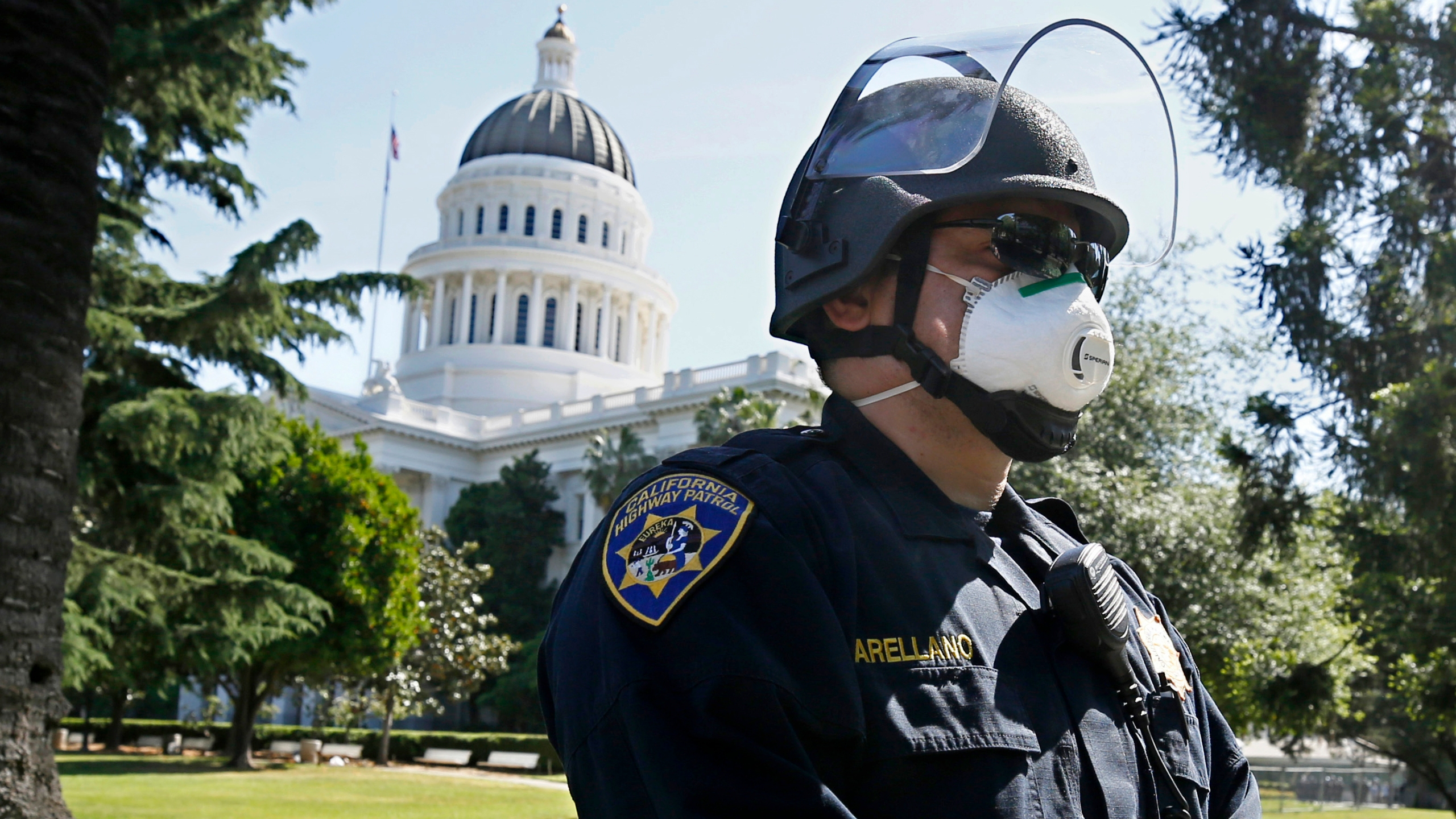 California Highway Patrol Officer S. Arellano wears a face mask as he and other officers form a line in anticipation of a protest at the the state Capitol in Sacramento on May 7, 2020. (Rich Pedroncelli / Associated Press)