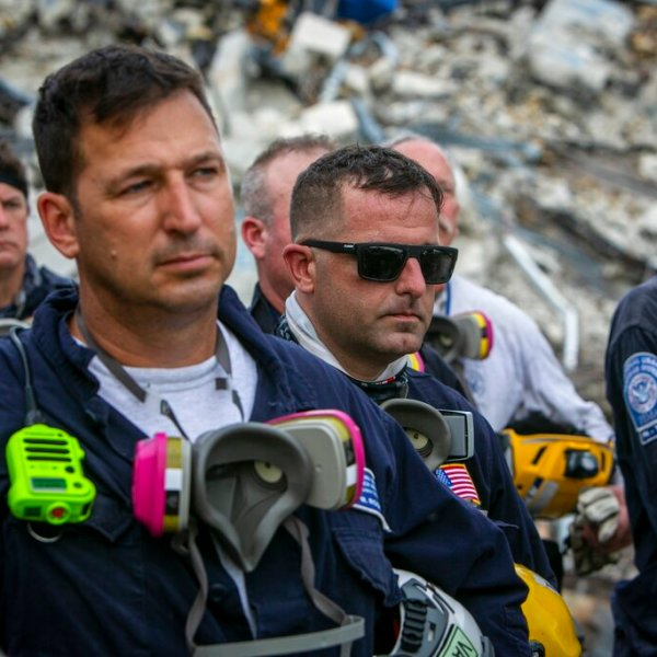 Members of a search and rescue team stand in front of the rubble that once was Champlain Towers South during a prayer ceremony in Surfside, Fla., Wednesday, July 7, 2021. (Jose A Iglesias/Miami Herald via AP)