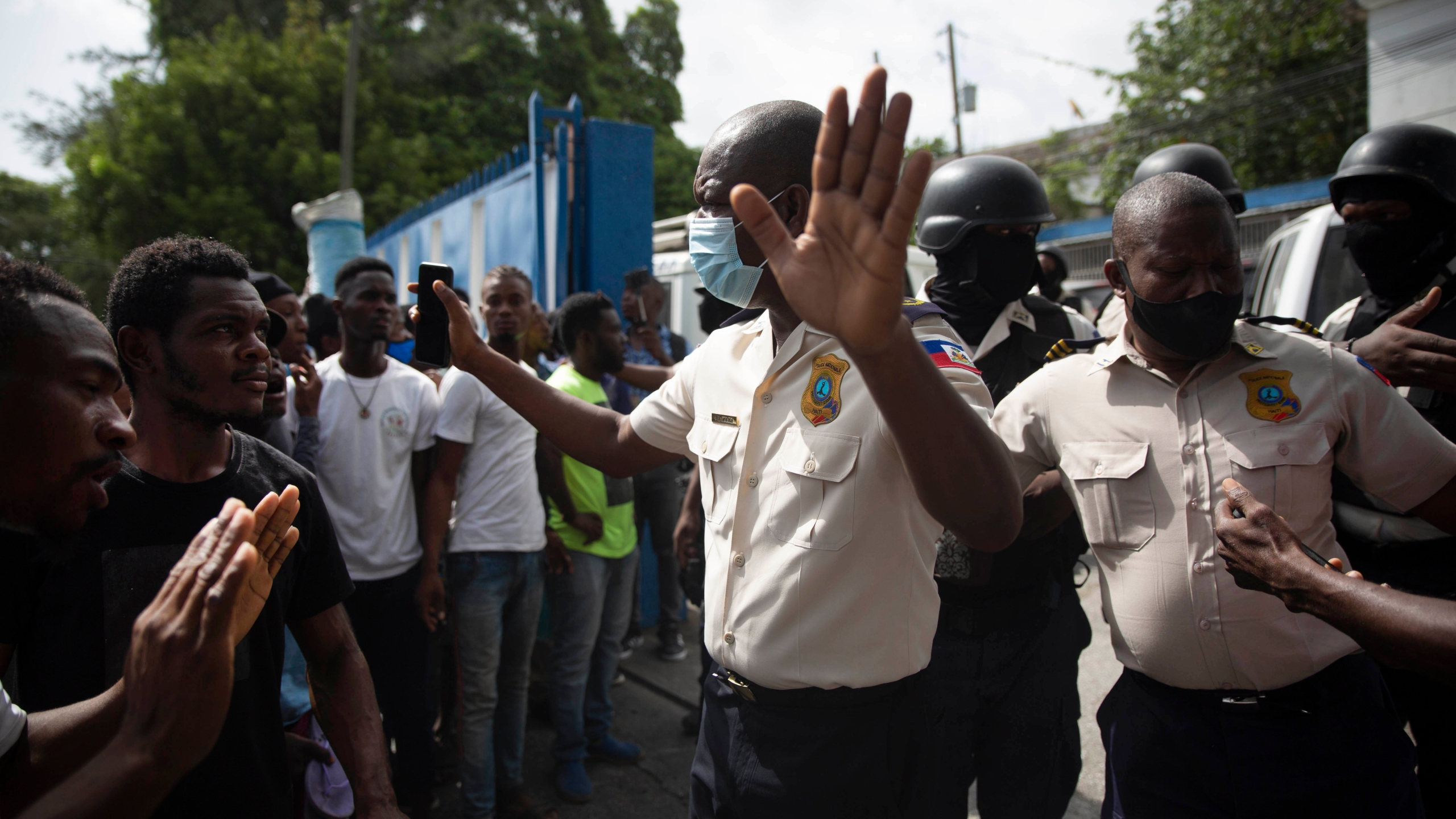 People pressure police to hand over two men who were arrested and the bodies of two men who were brought in by police after they were killed by police, in order to burn them in retaliation for the assassination of Haitian President Jovenel Moïse, at a police station of Petion Ville in Port-au-Prince, Haiti, Thursday, July 8, 2021. According to National Police Director Leon Charles, the dead and detained are suspects in Moïse's July 7 assassination. (AP Photo/Joseph Odelyn)