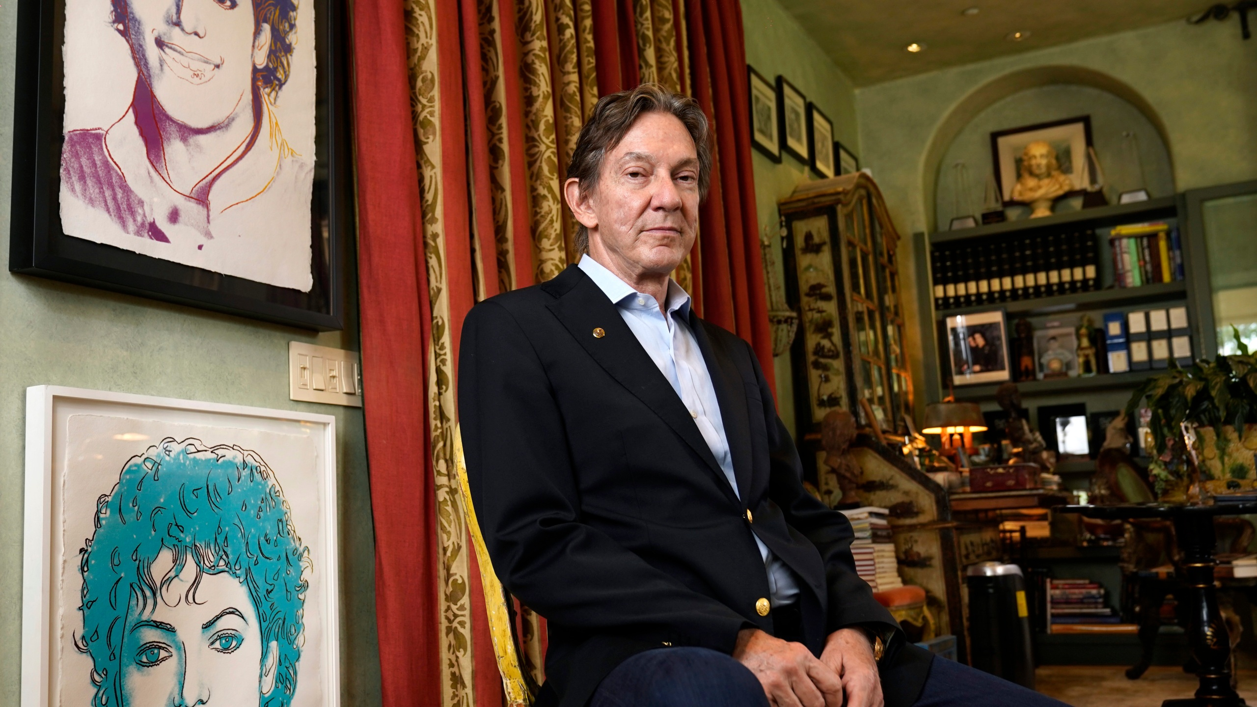 Entertainment lawyer and Michael Jackson Estate co-executor John Branca poses for a portrait alongside Andy Warhol prints of Jackson on July 8, 2021, at his home in Los Angeles. (Chris Pizzello/Associated Press)