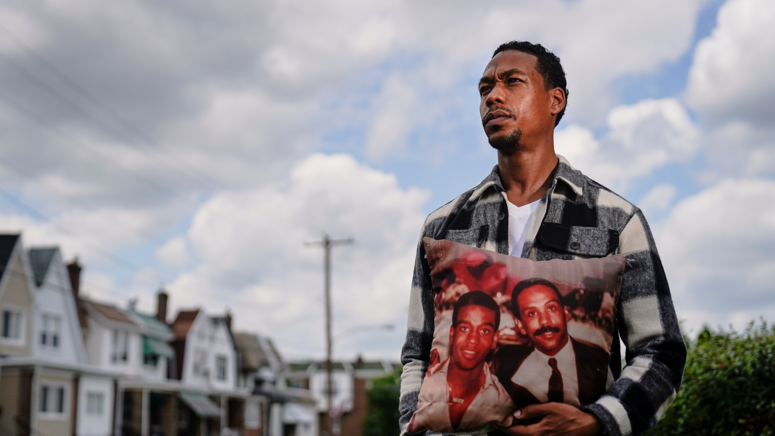 In this July 9, 2021, photo Brett Roman Williams poses for a photograph while holding a pillow with a photo of his father, Donald Williams, lower right, and brother Derrick Williams who both were killed by gunfire 20 years apart, in Philadelphia. (AP Photo/Matt Rourke)