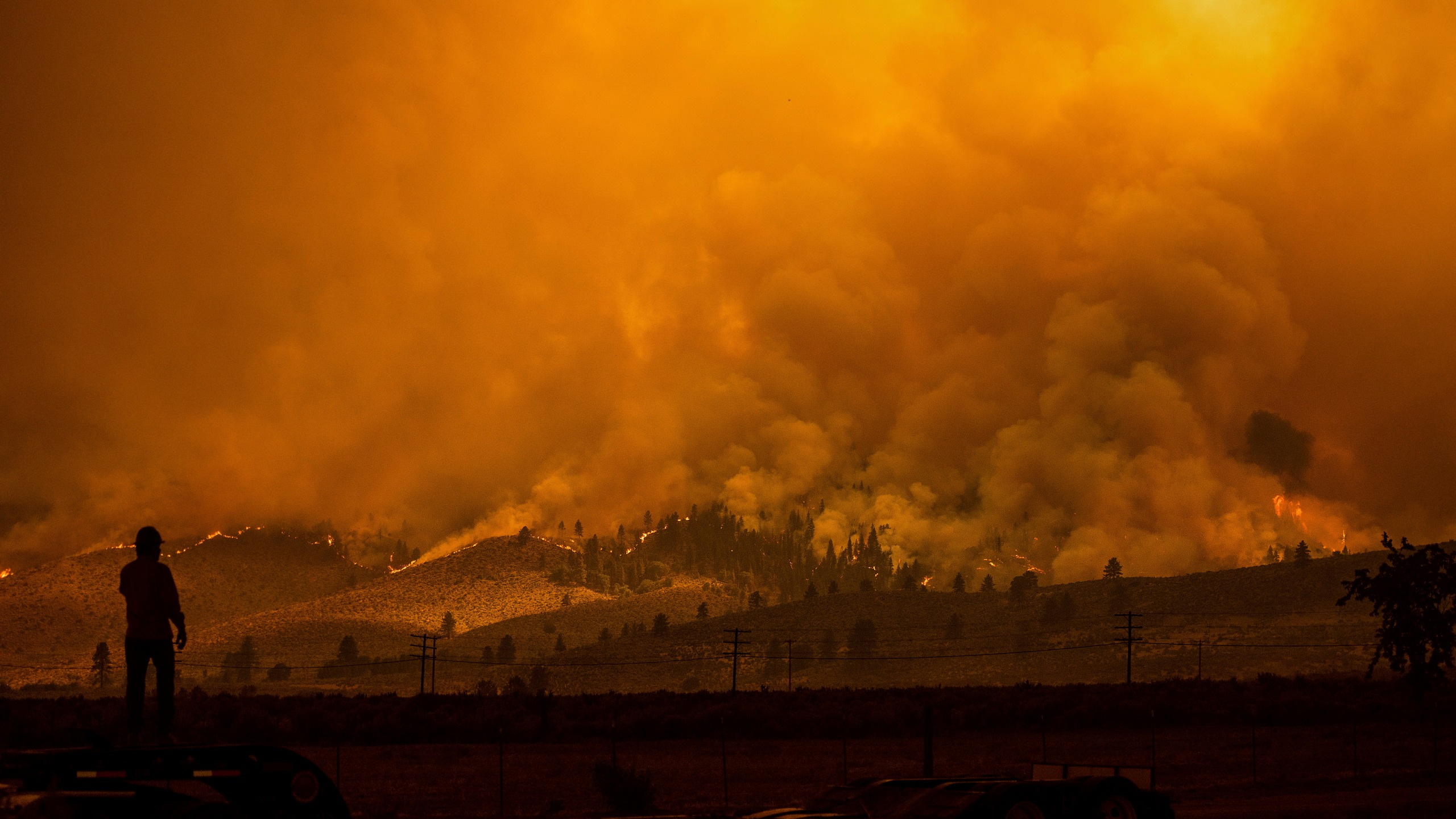 A truck driver who hauls fire equipment watches as the Sugar Fire, part of the Beckwourth Complex Fire, burns in Doyle, Calif., on Saturday, July 10, 2021. (AP Photo/Noah Berger)