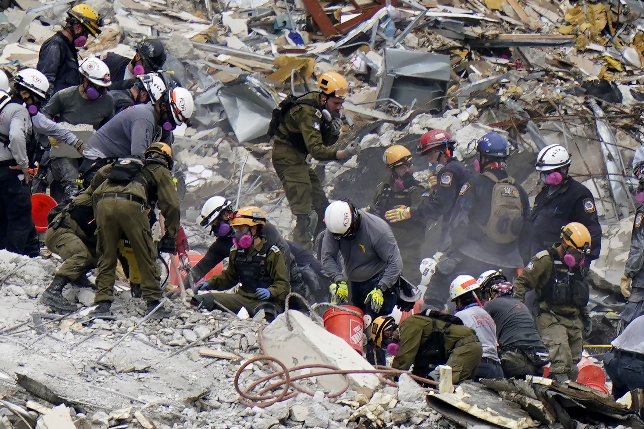 Crews from the United States and Israel work in the rubble Champlain Towers South condo, Tuesday, June 29, 2021, in Surfside, Fla. (AP Photo/Lynne Sladky, File)