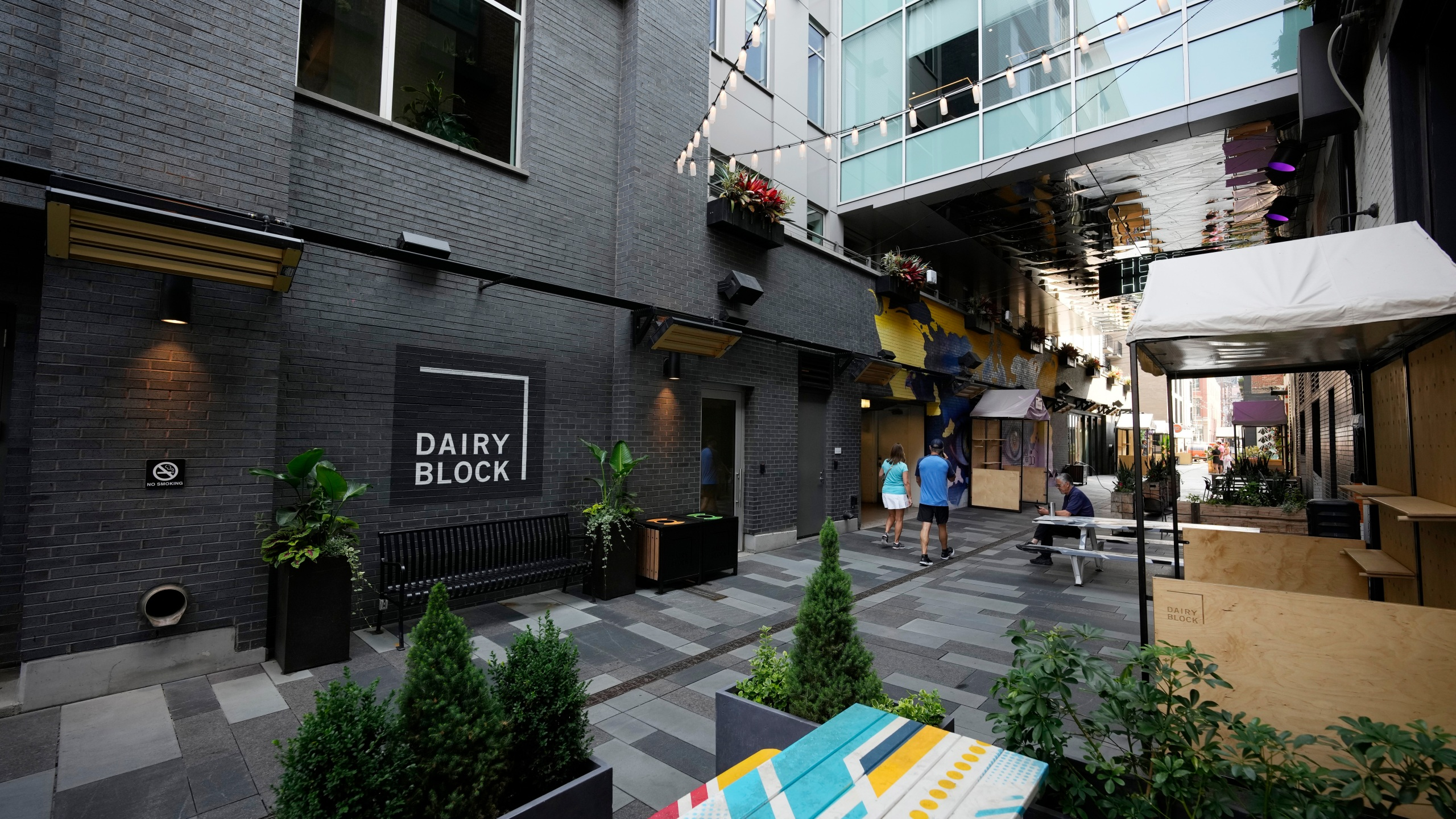 Pedestrians move through the alleyway in the Dairy Block and past the outside of the Maven Hotel Sunday, July 11, 2021, in lower downtown Denver. (AP Photo/David Zalubowski)