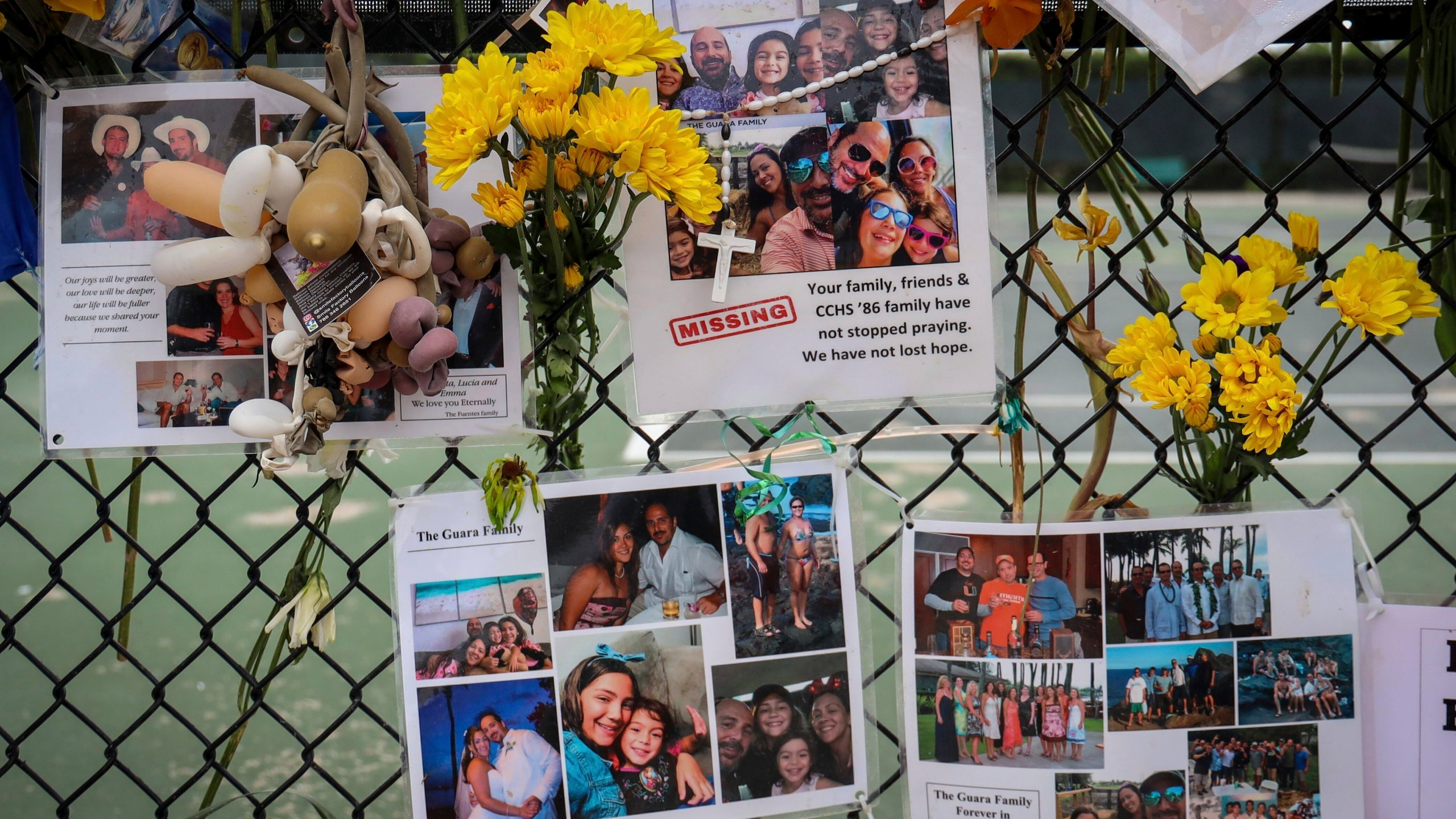 In this July 6, 2021, file photo, a memorial for the Guara family is posted on a fence near the Champlain Towers South, in Surfside, Fla. Recovery crews at the Florida condominium collapse are cataloging all personal possessions found in the rubble in hopes of returning them to families of the dead or survivors. (Carl Juste/Miami Herald via AP, File)