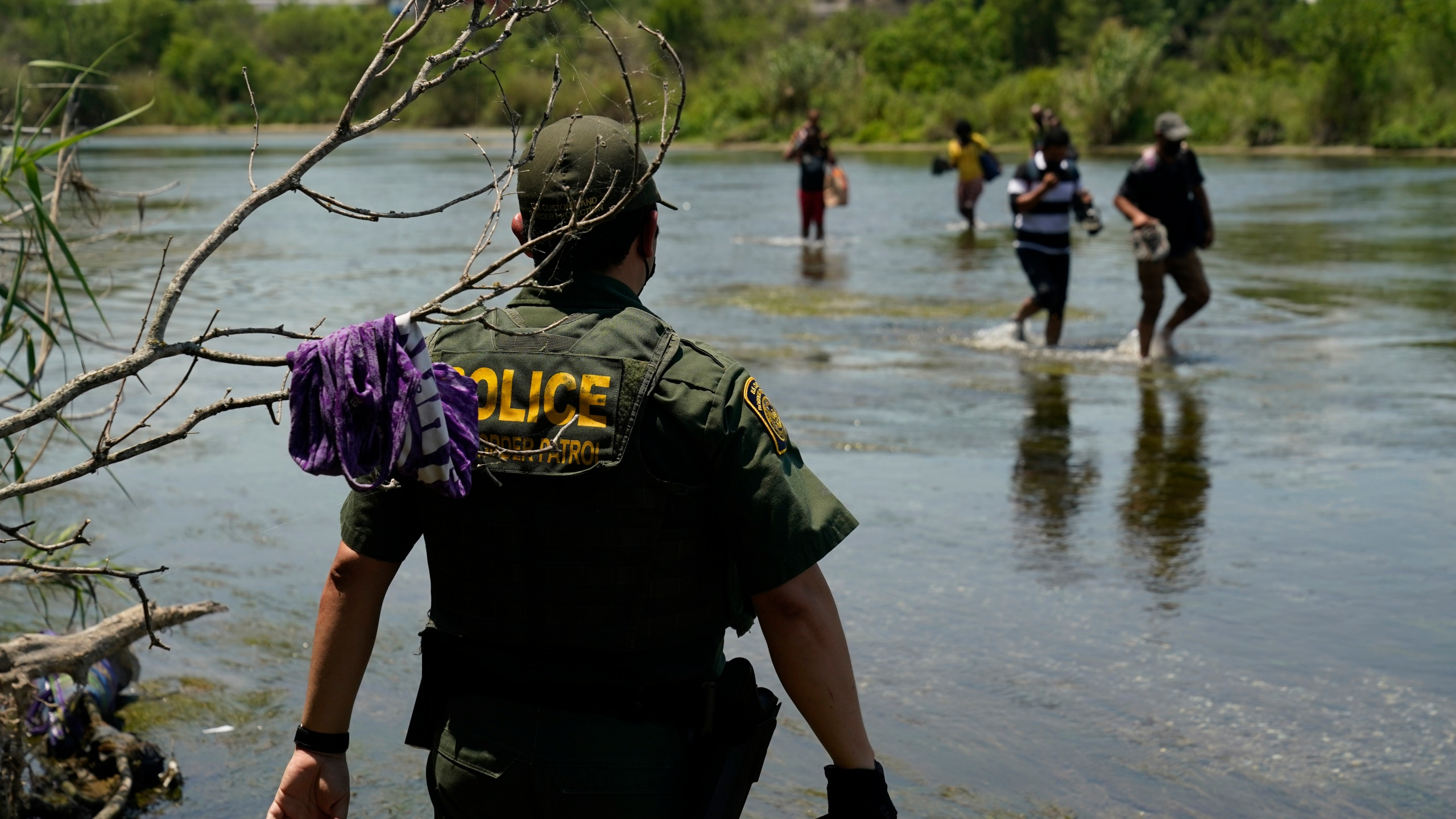 In this June 15, 2021, file photo, a Border Patrol agent watches as a group of migrants walk across the Rio Grande on their way to turning themselves in upon crossing the U.S.-Mexico border in Del Rio, Texas. A Justice Department attorney says the U.S. Centers for Disease Control and Prevention will issue an order this week about treatment of children under a public health order that has prevented migrants from seeking asylum at U.S. borders. (AP Photo/Eric Gay, File)