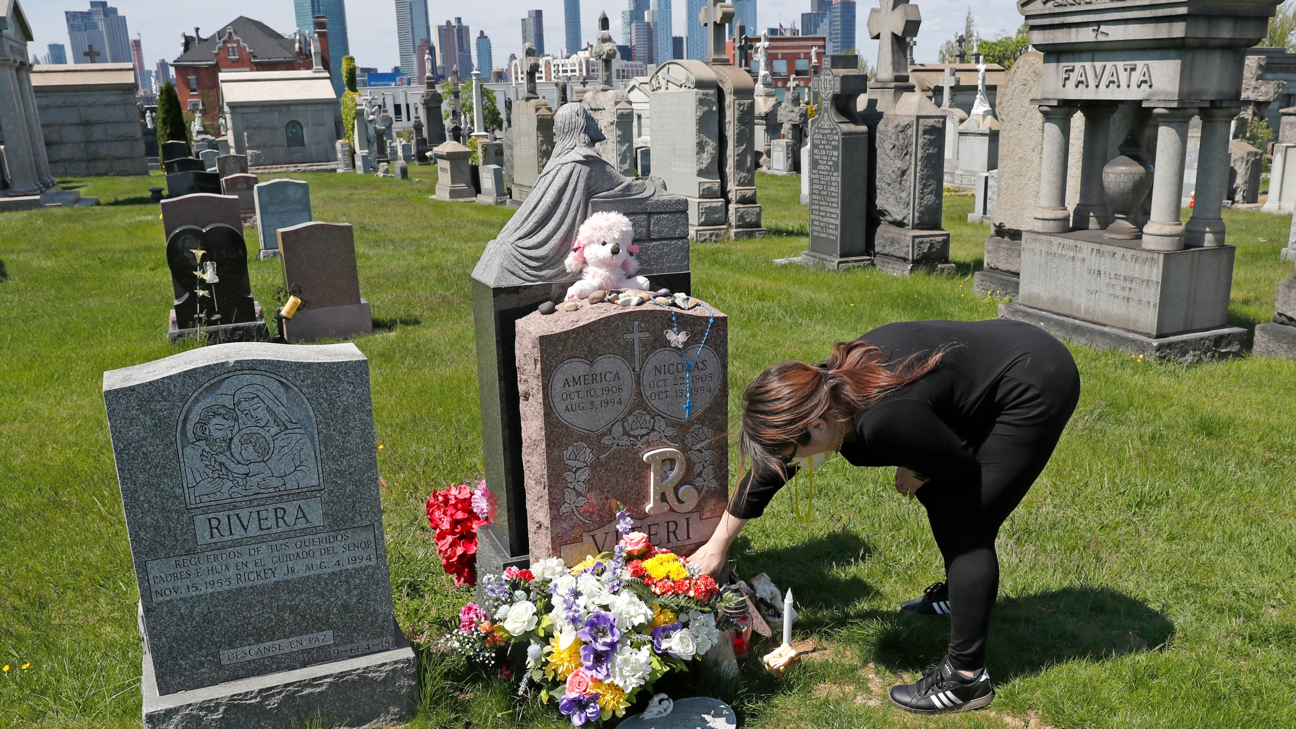 In this Sunday, May 10, 2020 file photo, Sharon Rivera adjusts flowers and other items left at the grave of her daughter, Victoria, at Calvary Cemetery in New York, on Mother's Day. Victoria died of a drug overdose in Sept. 22, 2019, when she just 21 years old. According to a report released by the Centers for Disease Control and Prevention on Wednesday, July 14, 2021, drug overdose deaths soared to a record 93,000 last year in the midst of the COVID-19 pandemic. (AP Photo/Kathy Willens, File)