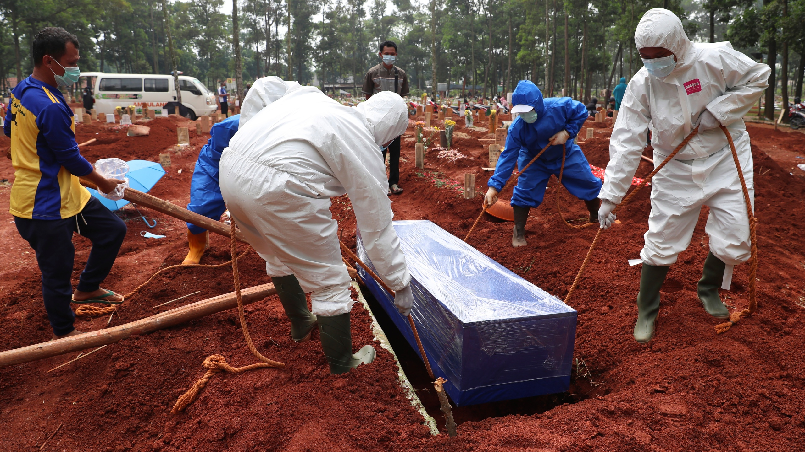 Workers in protective gear lower a coffin of a COVID-19 victim to a grave for burial at the Cipenjo Cemetery in Bogor, West Java, Indonesia on July 14, 2021. (Achmad Ibrahim/Associated Press)