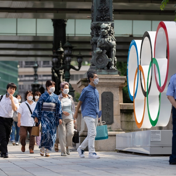 People walk by the Olympic rings installed by the Nippon Bashi bridge in Tokyo on Thursday, July 15, 2021. (Hiro Komae/Associated Press)