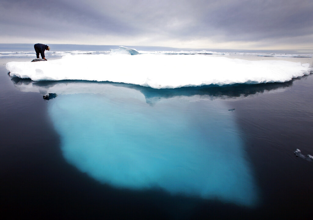 In this file photo dated July 2007, an Inuit seal hunter touches a dead seal atop a melting iceberg near Ammassalik Island, Greenland. (AP Photo/John McConnico, FILE)