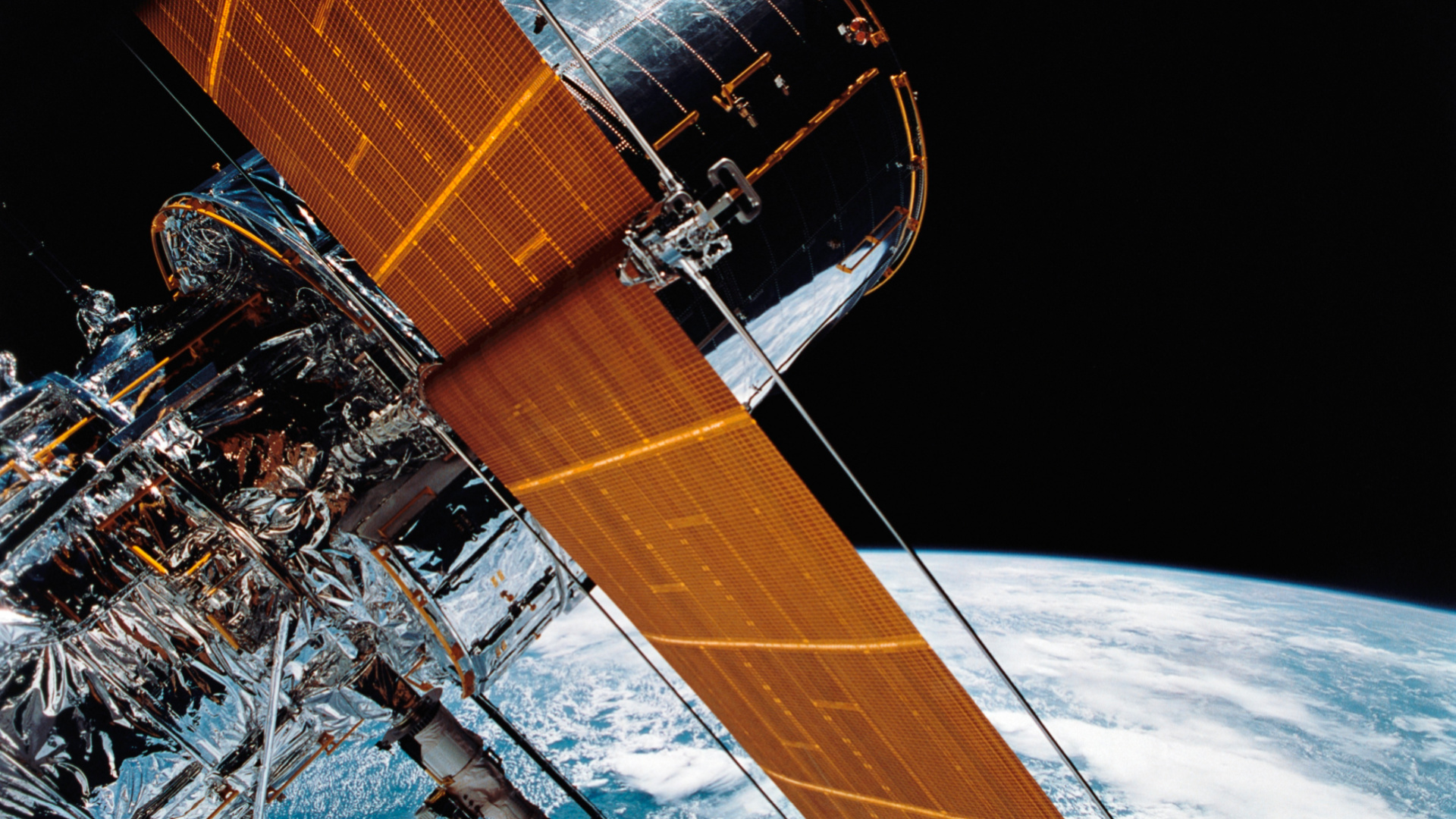 In this April 25, 1990 photograph provided by NASA, most of the giant Hubble Space Telescope can be seen as it is suspended in space by Discovery's Remote Manipulator System (RMS) following the deployment of part of its solar panels and antennae. (NASA via AP)