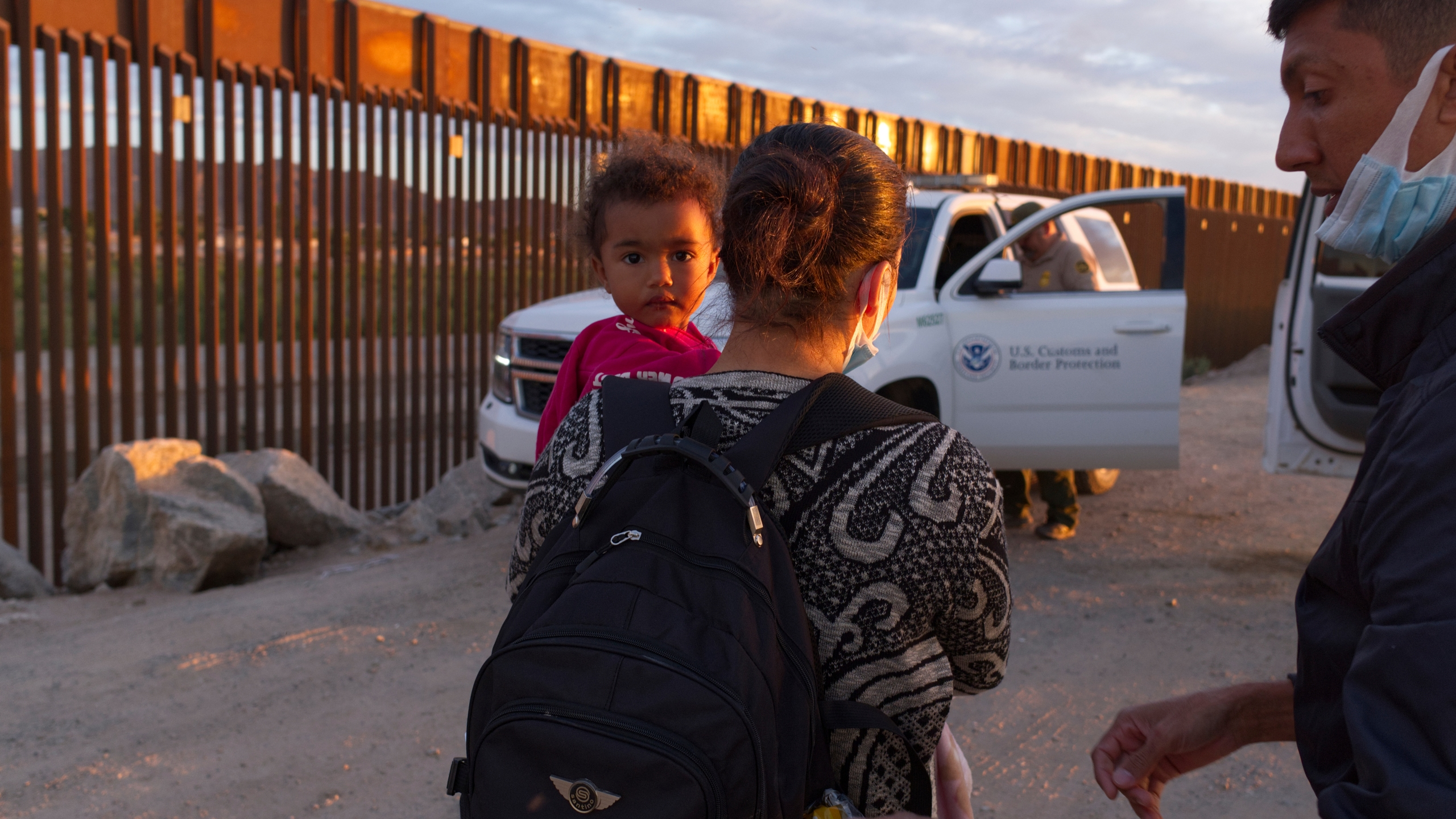 In this June 10, 2021, file photo, a migrant family from Brazil waits to be processed by U.S. Border Patrol agents after passing through a gap in the border wall from Mexico in Yuma, Ariz. U.S. officials say attempted border crossings by migrants traveling in family groups that include children increased in June by a quarter over the previous month amid rising summer temperatures in the inhospitable deserts and mountain terrain of the American Southwest. (AP Photo/Eugene Garcia, File)