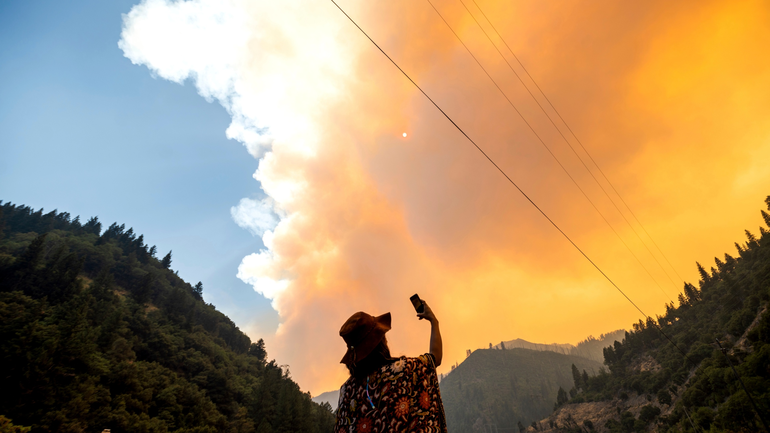 Jessica Bell takes a video as the Dixie Fire burns along Highway 70 in Plumas National Forest, Calif., on July 16, 2021. (AP Photo/Noah Berger)