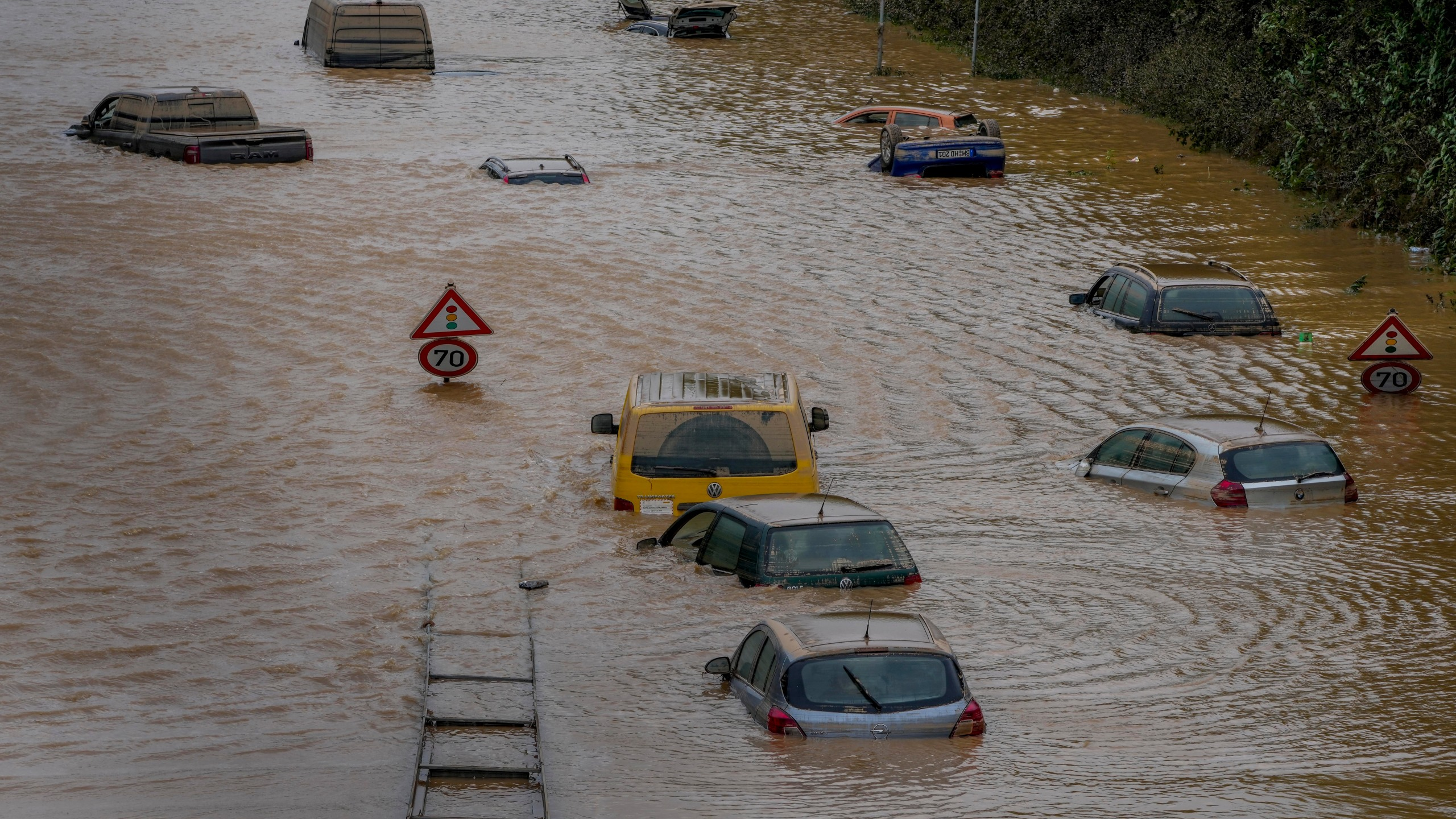 Cars show up as the flood sinks on a road in Erftstadt, Germany, Saturday, July 17, 2021. Due to strong rain falls the small Erft river went over the banks causing massive damages. (AP Photo/Michael Probst)