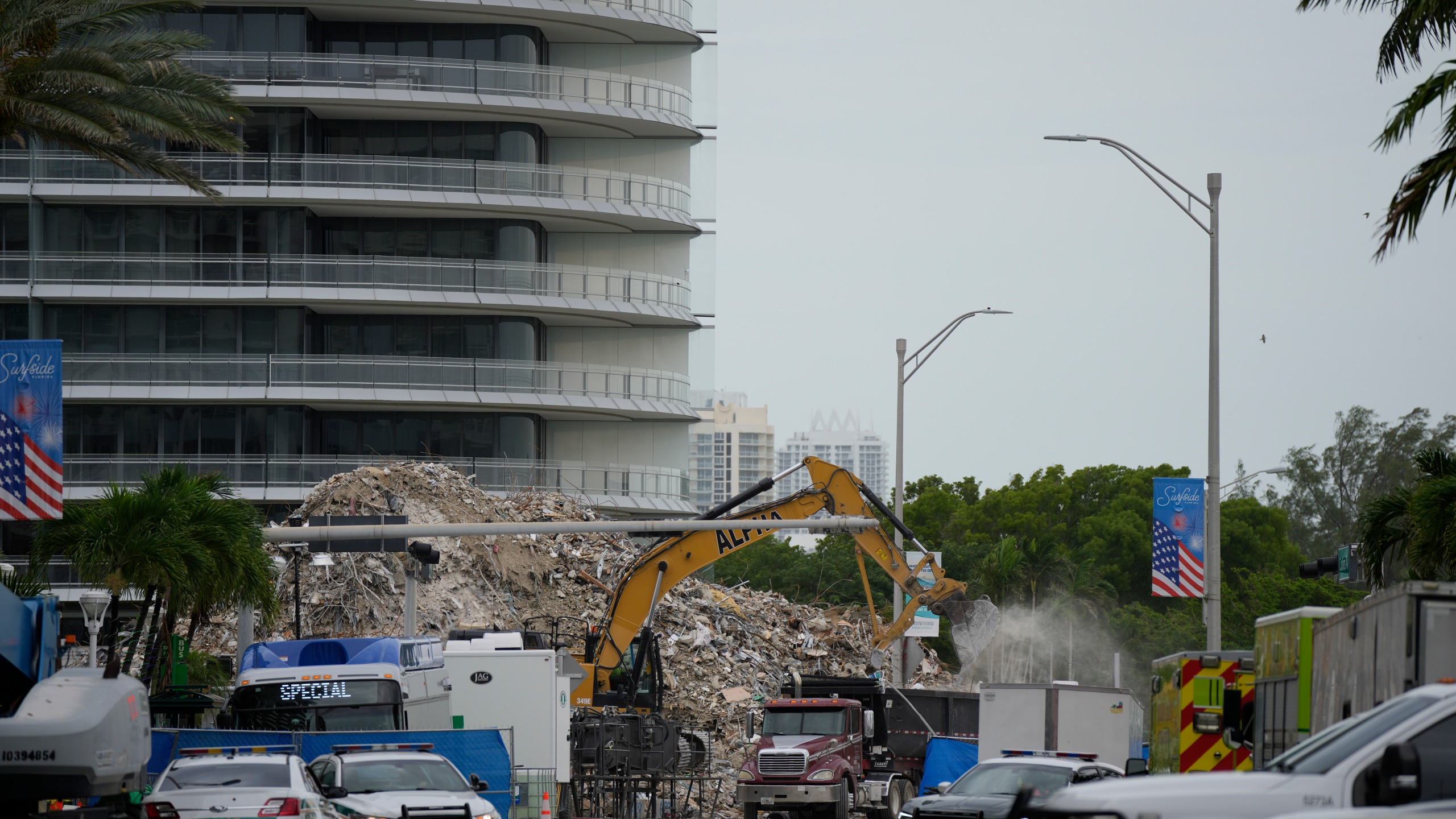 In this July 12, 2021 file photo, an excavator removes the rubble of the demolished section of the Champlain Towers South building, as recovery work continues at the site of the partially collapsed condo building, in Surfside, Fla. Another victim has been identified in the collapse of a 12-story Florida condominium. The Miami-Dade Police Department said in a news release Saturday, July 17, that Theresa Velasquez, 36, was a confirmed fatality in the June 24 collapse of the Champlain Towers South condo. (AP Photo/Rebecca Blackwell, File)