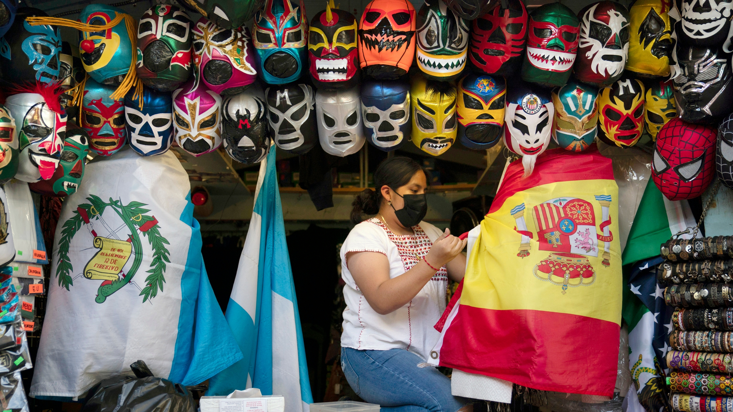 In this June 8, 2021, file photo, clerk Wendy Ramirez uses a Spanish flag to wrap souvenirs while preparing to close the store for the day on Olvera Street in Los Angeles. Los Angeles County residents are again required to wear masks indoors regardless of their vaccination status, a new mandate starting this weekend that health officials hope will reverse the latest spikes in coronavirus cases, hospitalizations and deaths. The rule went into effect late Saturday, July 17, for the nation's largest county, home to 11 million people, where a sharp increase in COVID-19 cases is led by the highly transmissible delta variant. (AP Photo/Jae C. Hong, File)