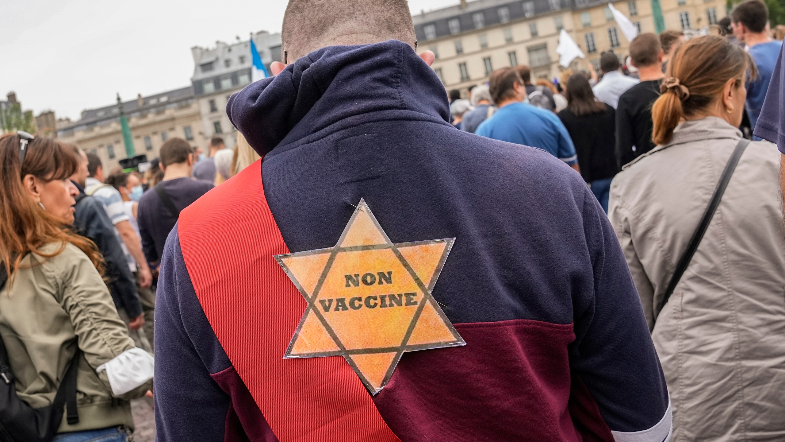 A star that reads, not vaccinated is attached on the back of an Anti-vaccine protesters during a rally in Paris, Saturday, July 17, 2021. A Holocaust survivor, French officials and anti-racism groups are denouncing anti-vaccination protesters who are comparing themselves to Jews persecuted by the Nazis. Some mostly far-right demonstrators at weekend protests against government vaccine rules wore yellow stars, like those Jews were forced to wear under Nazi rule in World War II. Other demonstrators carried signs evoking the Auschwitz death camp or South Africa's apartheid regime, claiming the French government is unfairly persecuting them as it battles the pandemic. (AP Photo/Michel Euler, File)