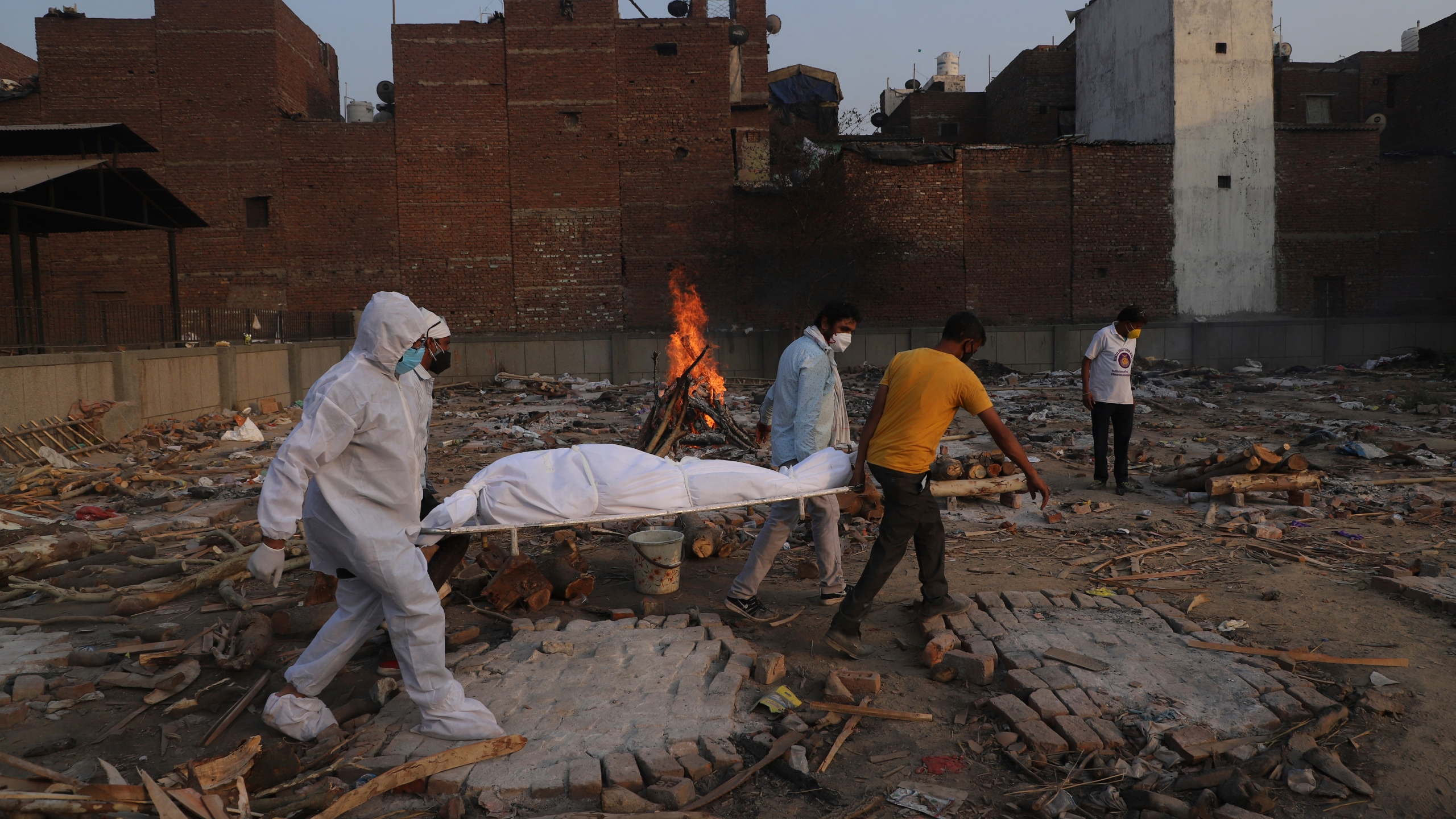In this May 11, 2021, file photo, family members and volunteers carry the body of a COVID-19 victim for cremation in New Delhi, India. (Amit Sharma/Associated Press)