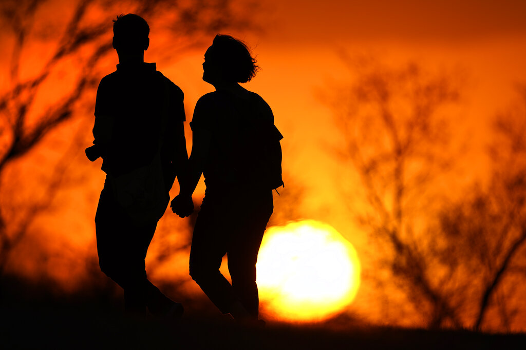 In this Wednesday, March 10, 2021 file photo, a couple walks through a park at sunset in Kansas City, Mo. (AP Photo/Charlie Riedel, File)