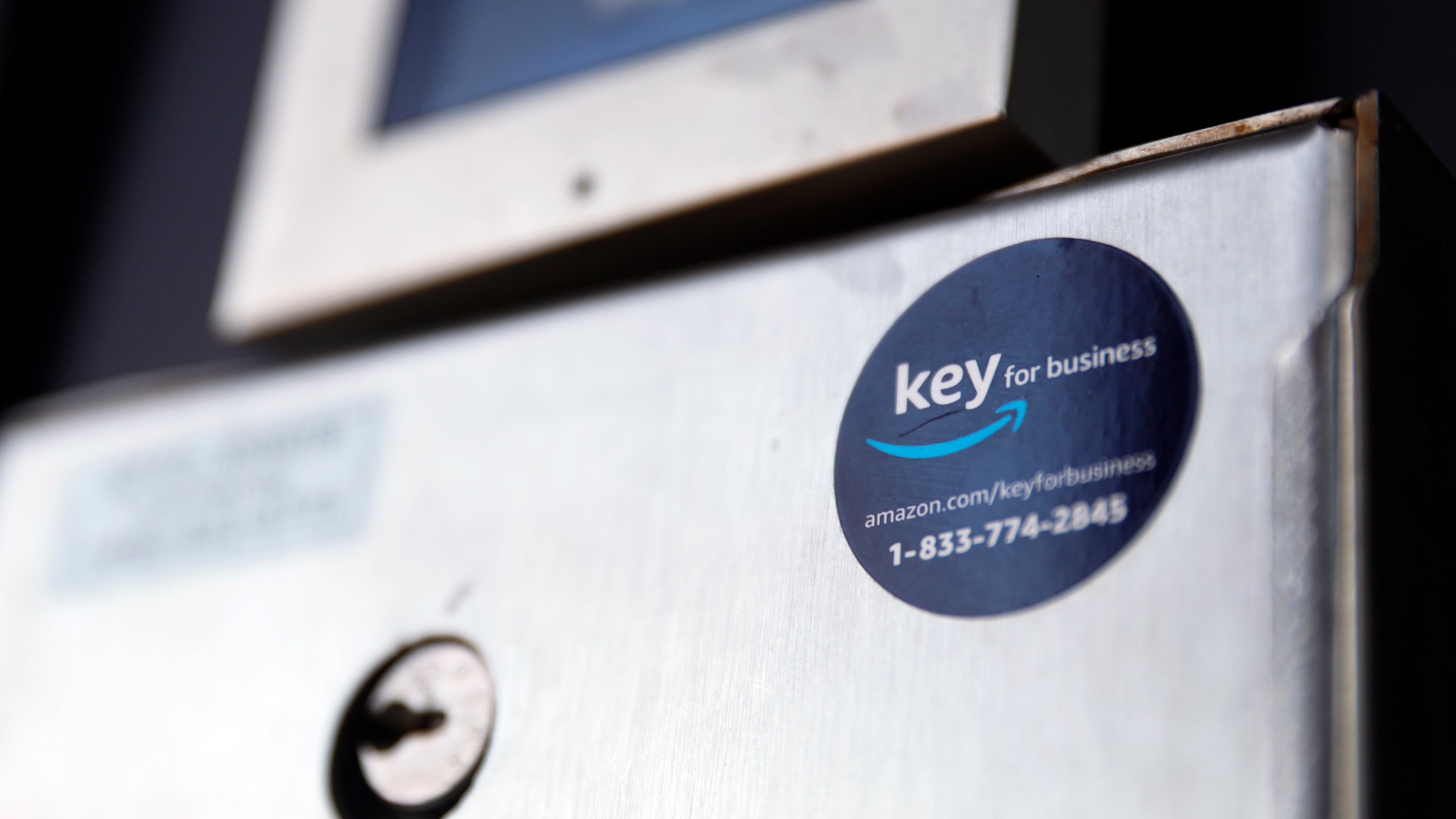 A blue sticker with the Amazon logo is displayed on a buzzer system in the apartment building of Jason Goldberg, chief commerce strategy officer at marketing company Publicis Communications, Monday, March 29, 2021, in Chicago. (AP Photo/Shafkat Anowar)