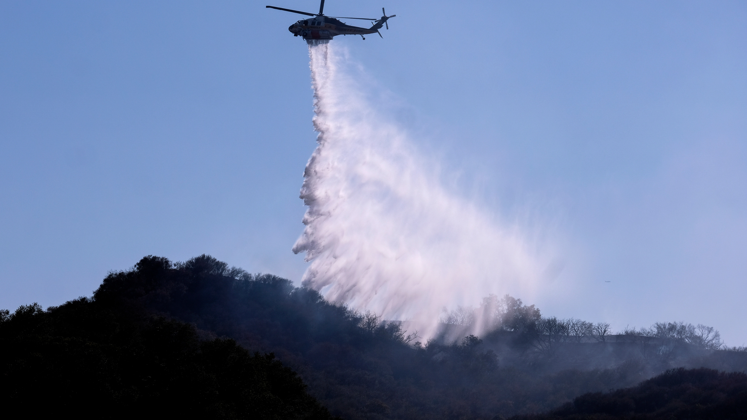 A helicopter makes a water drop to put out hotspots in a wildfire in Topanga, west of Los Angeles, Monday, July 19, 2021. (AP Photo/Ringo H.W. Chiu)