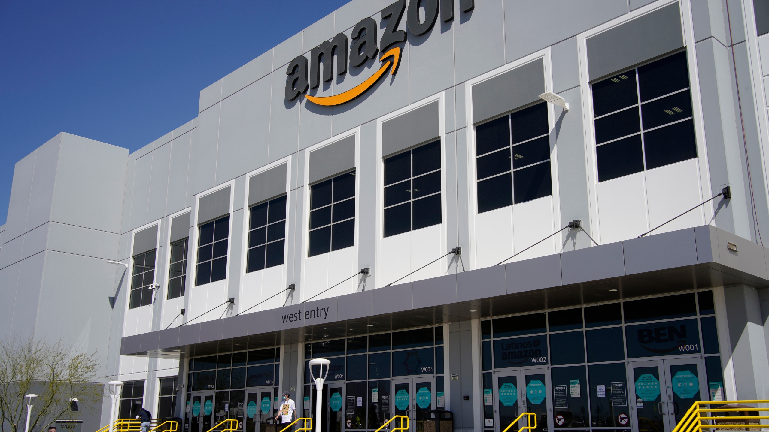 A worker walks out of an Amazon Fulfillment Center, Wednesday, March 31, 2021, in North Las Vegas. Amazon said it will stop testing its workers for COVID-19 at its warehouses at the end of July, citing the availability of vaccines and free testing. (AP Photo/John Locher)