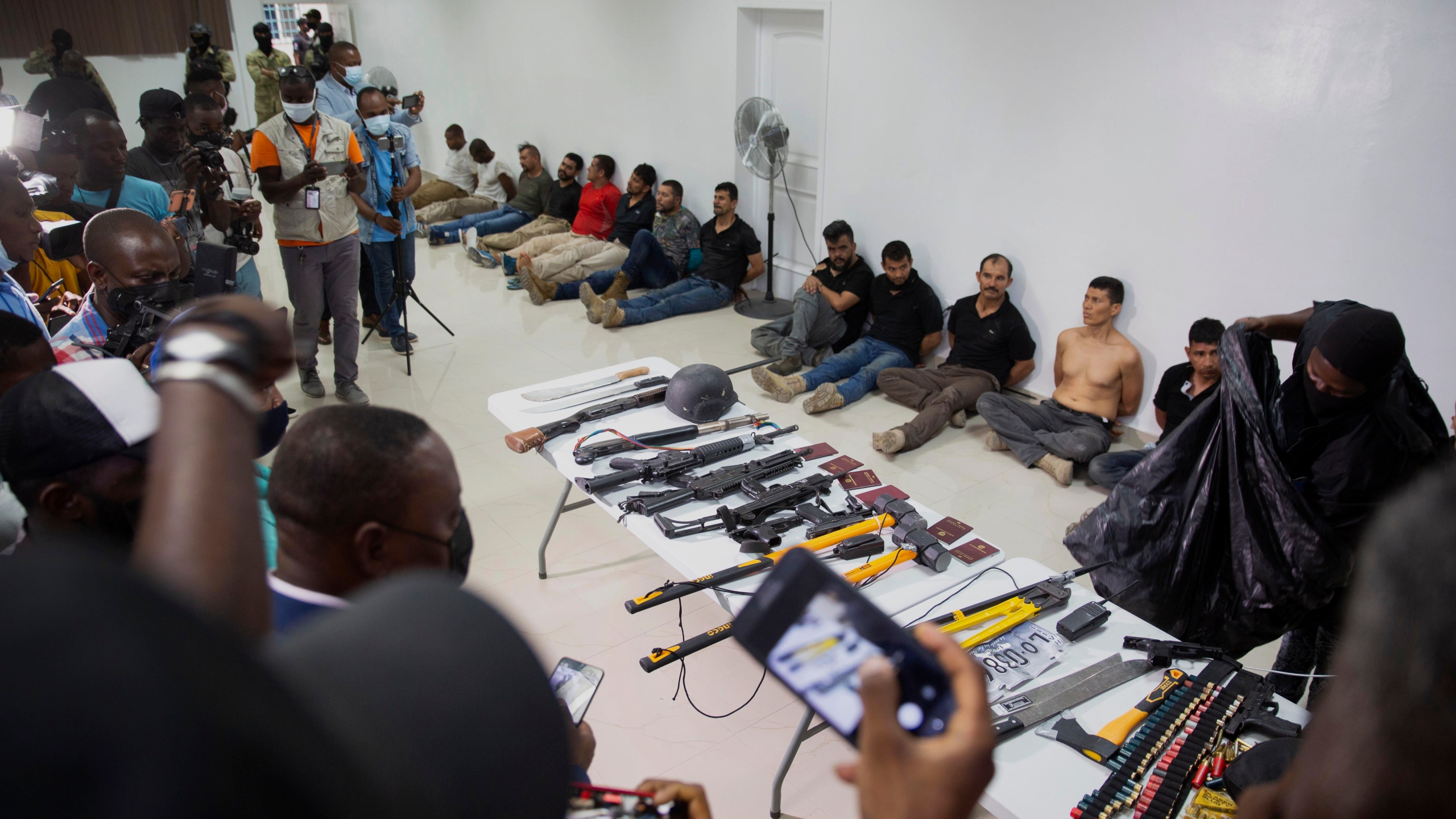 In this July 8, 2021 file photo, suspects in the assassination of Haiti's President Jovenel Moise are shown to the media, along with the weapons and equipment they allegedly used in the attack, at police headquarters in Port-au-Prince. (Jean Marc Hervé Abélard/Associated Press)