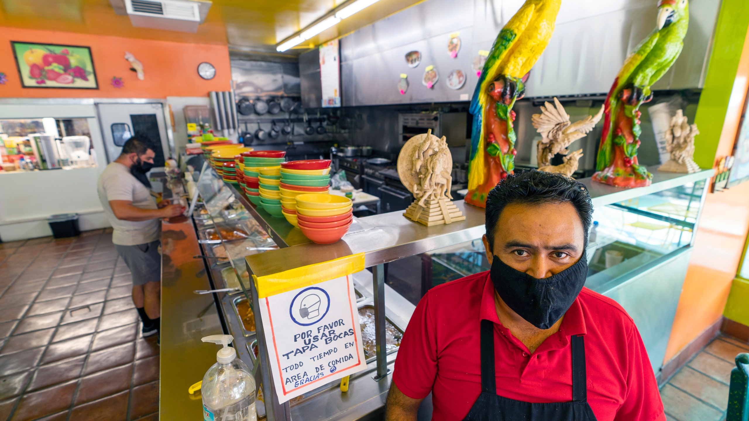 Adrian Luna, owner of the Taqueria El Sol buffet in Los Angeles' Boyle Heights neighborhood, stands in the buffet area of his restaurant in Los Angeles, Thursday, July 22, 2021. Luna requires all his customers to wear face masks. (AP Photo/Damian Dovarganes)