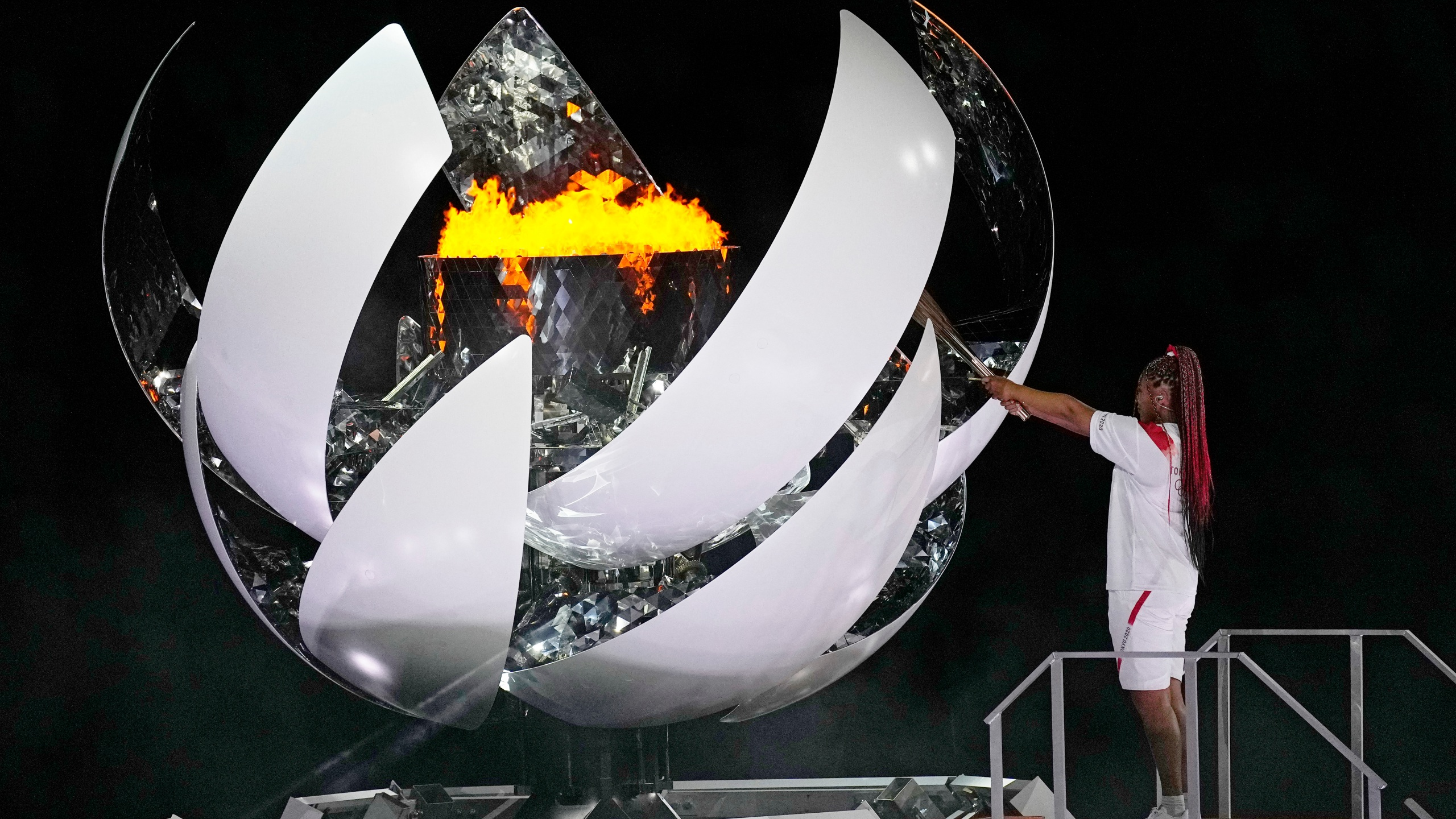 Naomi Osaka lights the Olympic flame during the opening ceremony in the Olympic Stadium at the 2020 Summer Olympics on July 23, 2021, in Tokyo. (David J. Phillip/Associated Press)