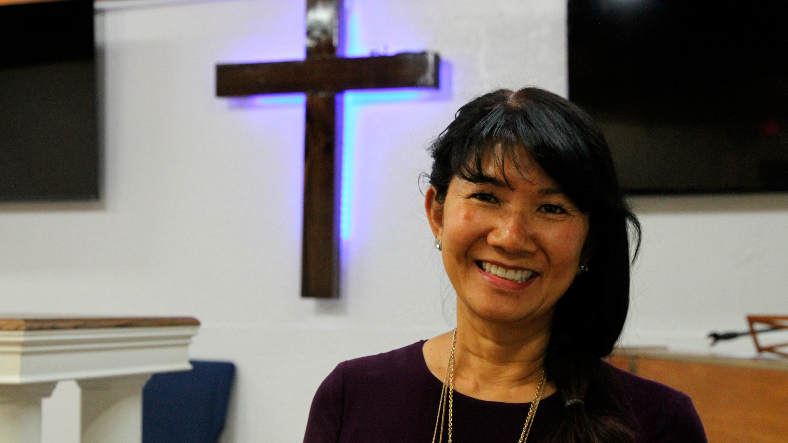 In this May 24, 2021, photo, Linda Dunegan poses for a photo in the sanctuary of the Open Door Baptist Church in Anchorage, Alaska. Dunegan purchased a former strip club and leased the main floor to the church. (AP Photo/Mark Thiessen)