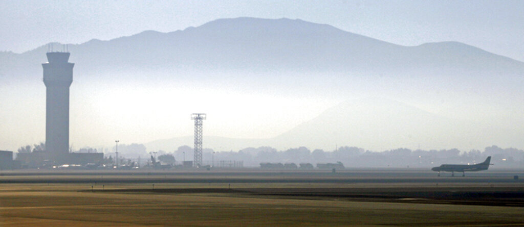 In this Sept. 24, 2014 file photo, smoke hangs over Reno-Tahoe International Airport as a plane takes off in Reno, Nevada. (AP Photo/Martha Irvine, File)