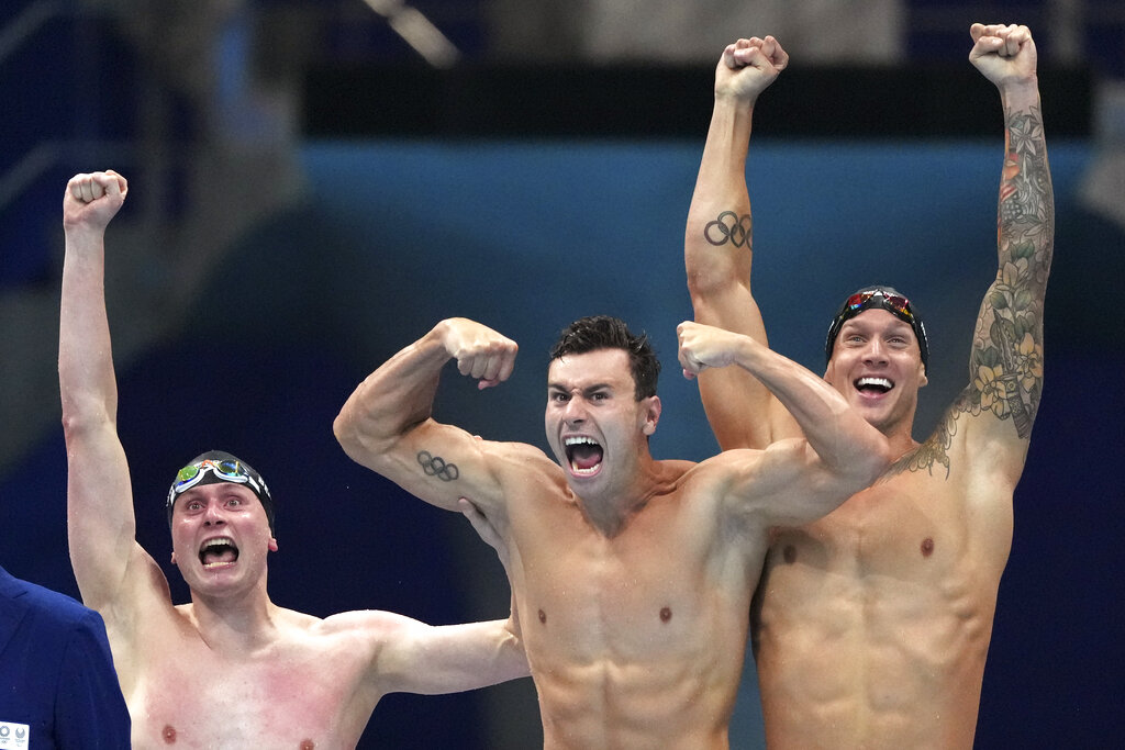 United States men's 4x100m freestyle relay team Bowen Beck, Blake Pieroni, and Caeleb Dressel celebrate after winning the gold medal at the 2020 Summer Olympics, Monday, July 26, 2021, in Tokyo, Japan. (AP Photo/Matthias Schrader)
