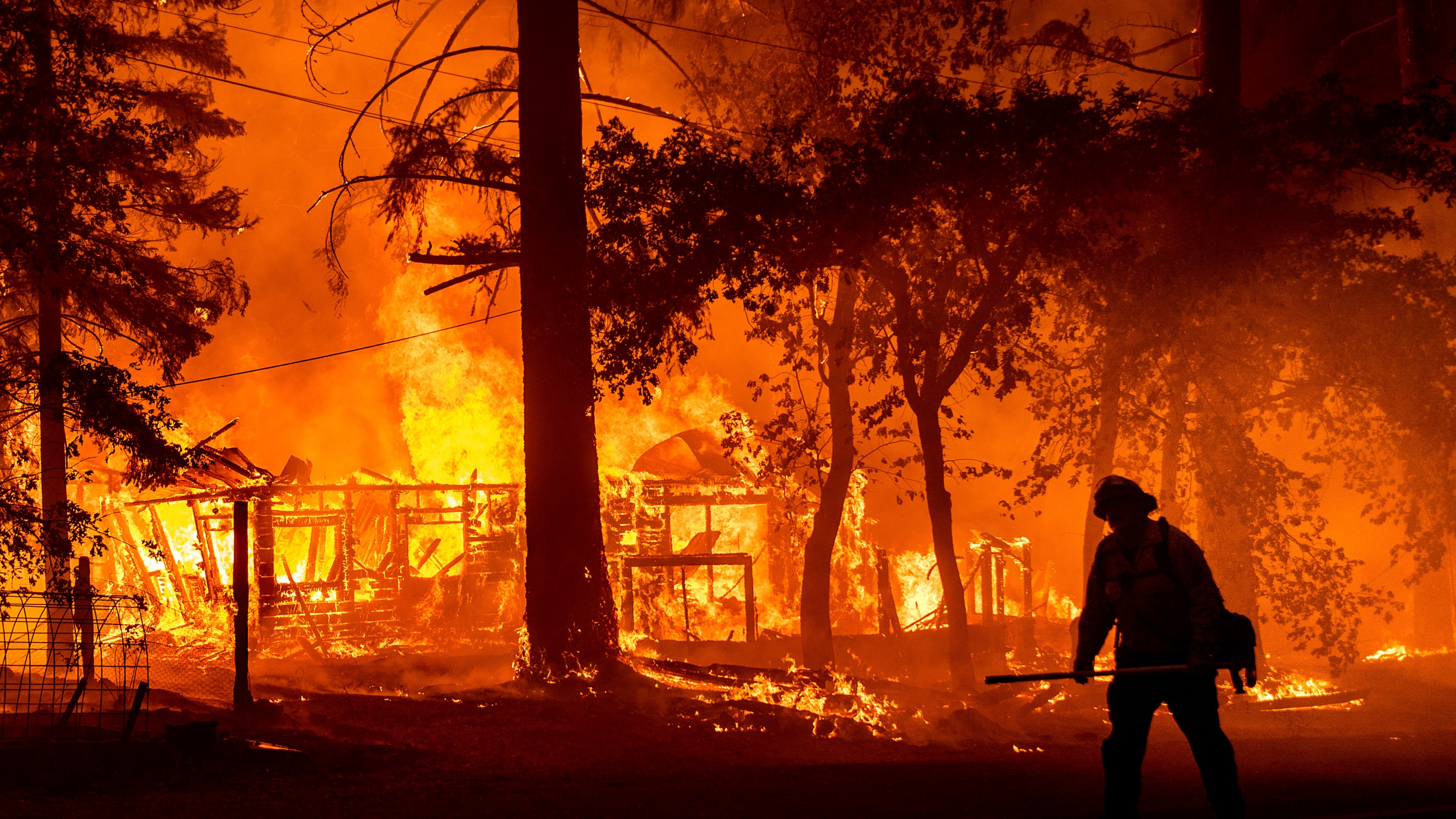 In this Saturday, July 24, 2021, file photo a firefighter passes a burning home as the Dixie Fire flares in Plumas County, Calif. The fire destroyed multiple residences as it tore through the Indian Falls community. Erratic winds and the potential for dry lightning added to the challenges facing firefighters battling California's largest wildfire, one of numerous blazes burning Monday across the U.S. West. (AP Photo/Noah Berge,File)