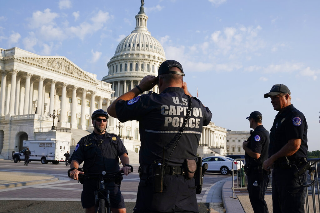 The U.S. Capitol is seen in Washington, early Tuesday, July 27, 2021, as U.S. Capitol Police watch the perimeter. (AP Photo/J. Scott Applewhite)