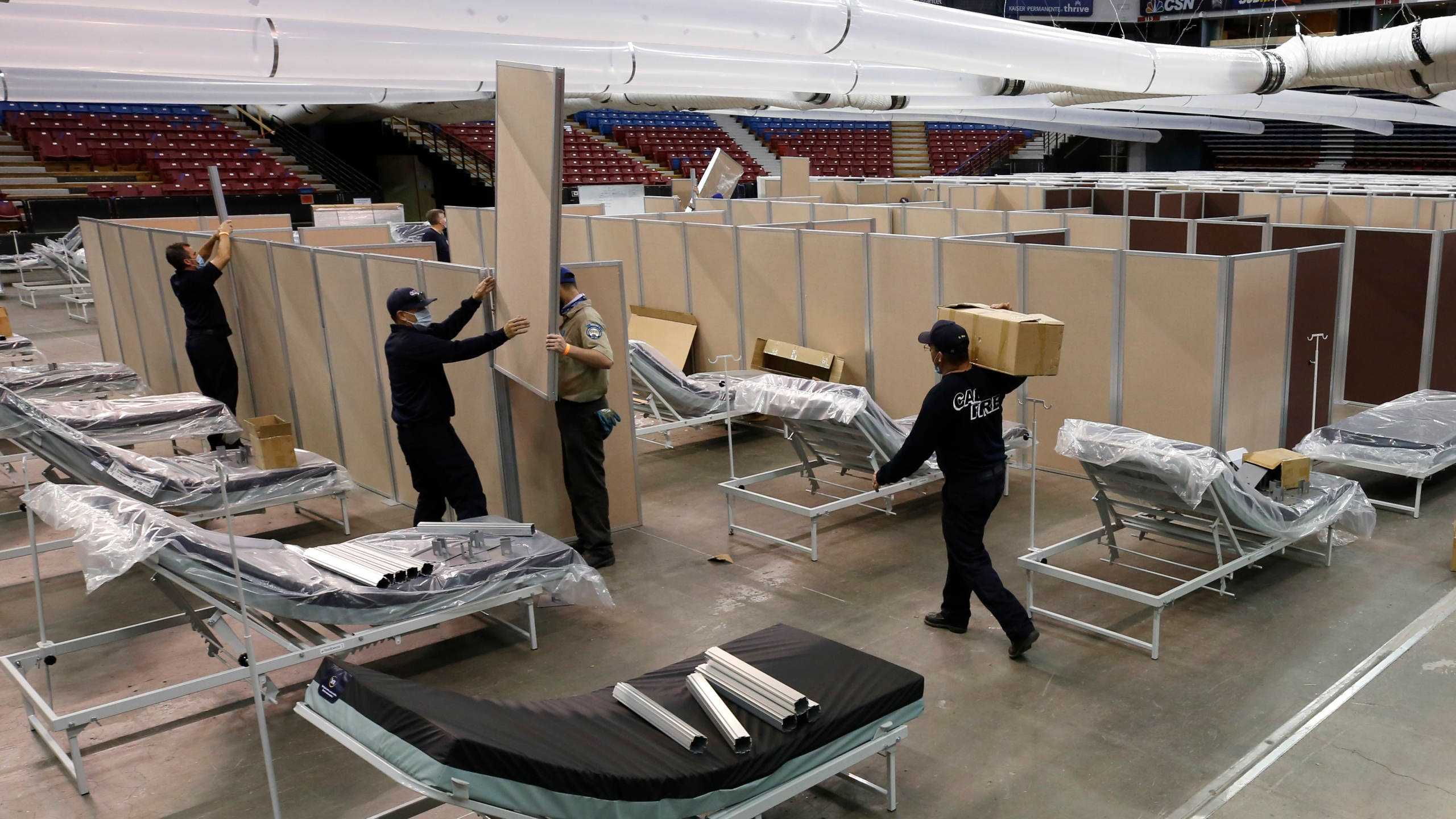 In this April 18, 2020 file photo partitions are installed between beds as work is performed to turn the Sleep Train Arena into a 400 bed emergency field hospital to help deal with the coronavirus, in Sacramento, Calif. (AP Photo/Rich Pedroncelli, File)