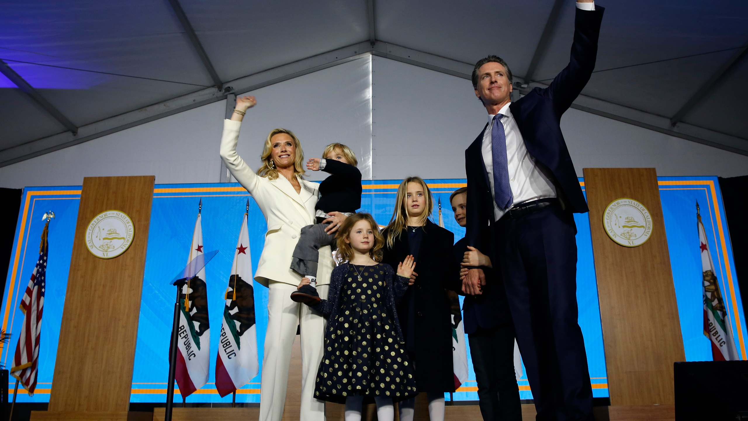 In this Jan. 7, 2019, file photo California Governor Gavin Newsom his wife, Jennifer Siebel Newsom, and their children wave after taking the oath office during his inauguration as 40th Governor of California, in Sacramento, Calif. Newsom's office said, Tuesday, July 27, 2021, that he pulled his children out of summer camp after children at the camp weren't wearing face masks, a violation of state policy. (AP Photo/Rich Pedroncelli, File)