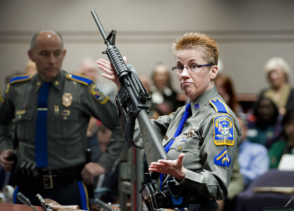 In this Jan. 28, 2013, file photo, firearms training unit Detective Barbara J. Mattson, of the Connecticut State Police, holds up a Bushmaster AR-15 rifle. (AP Photo/Jessica Hill, File)