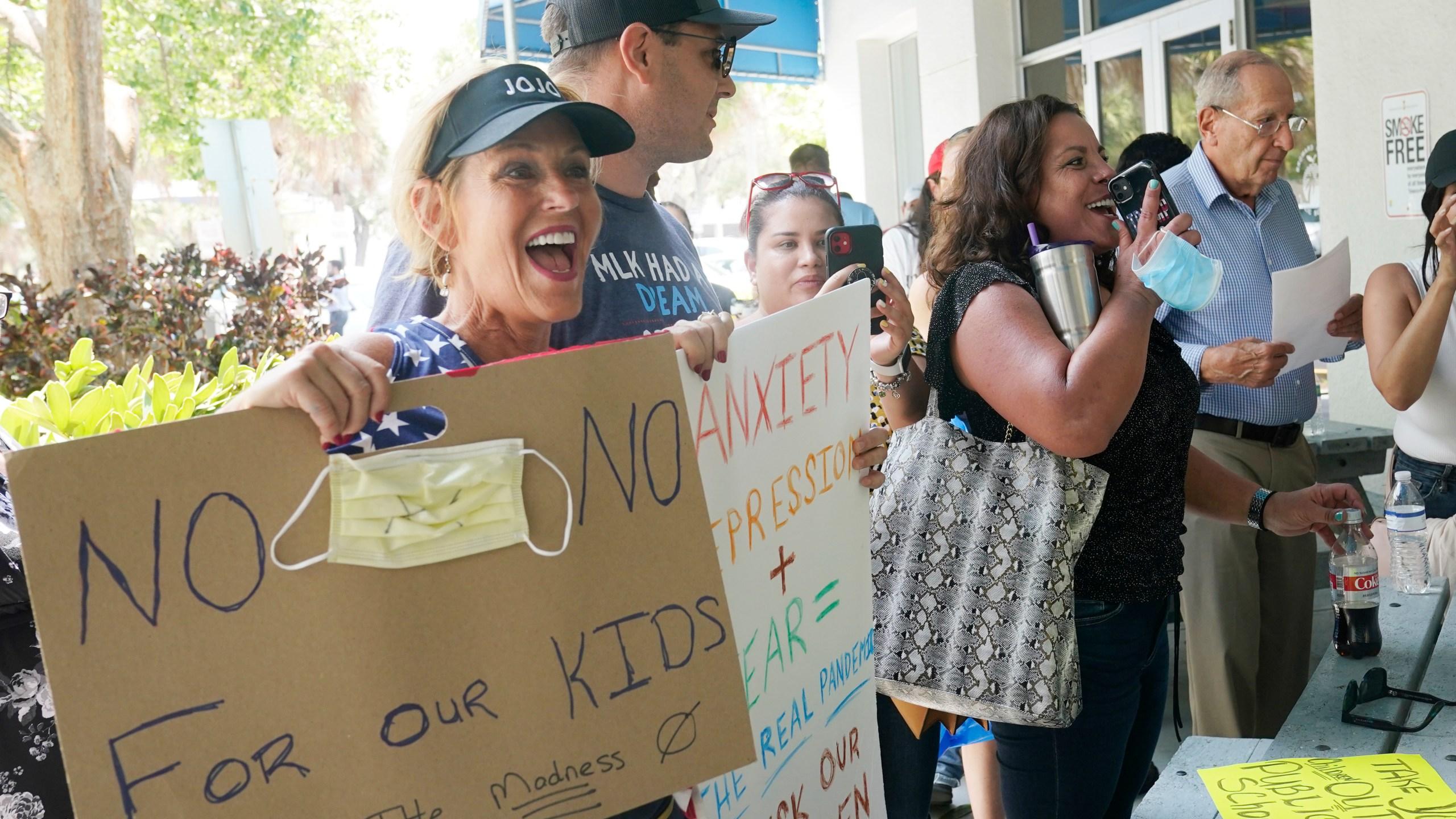 Joann Marcus of Fort Lauderdale, left, cheers as she listens to the Broward School Board's emergency meeting, Wednesday, July 28, 2021, in Fort Lauderdale, Fla. (AP Photo/Marta Lavandier)