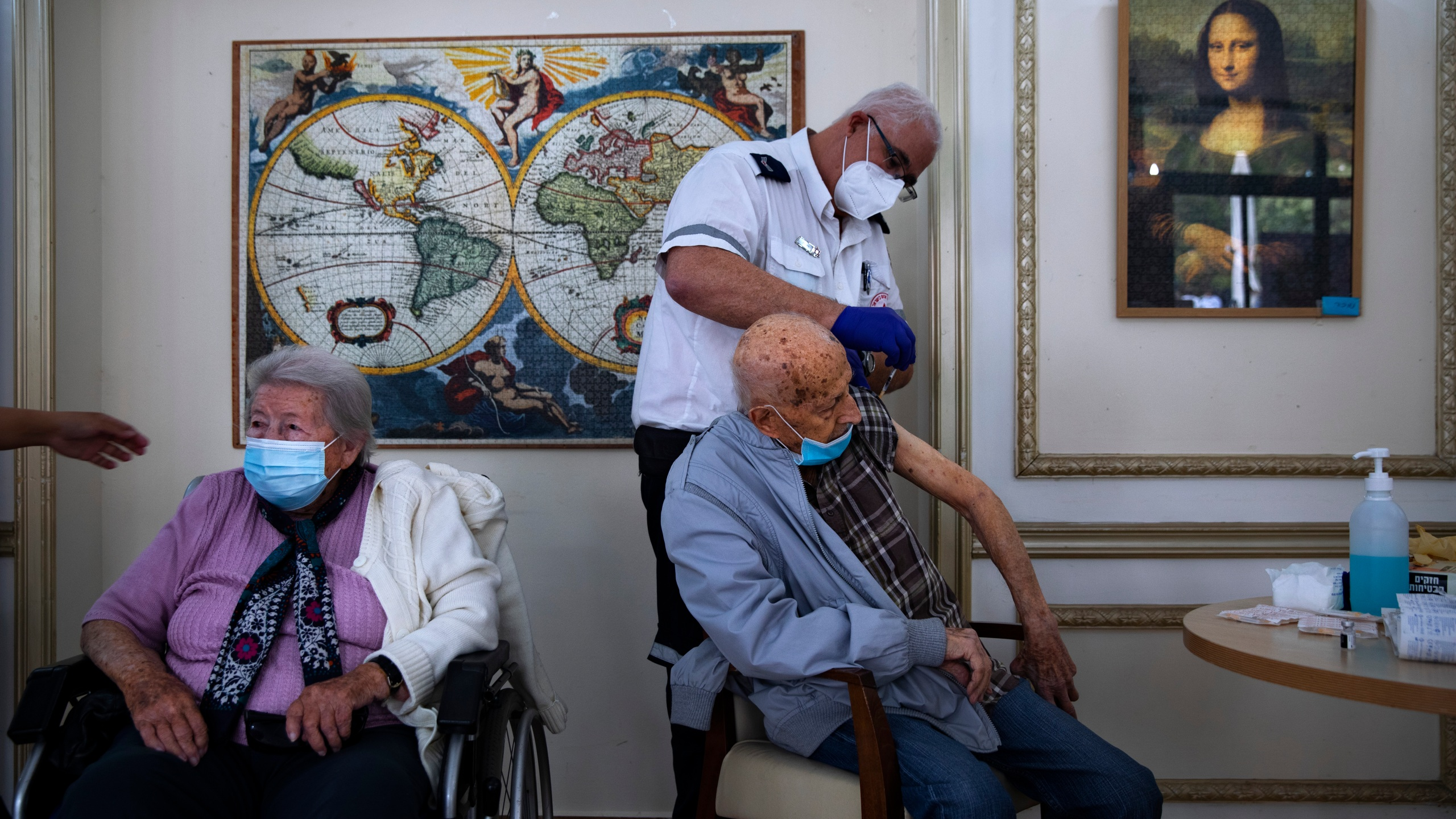 In this Jan. 13, 2021, file photo, a man receives his second Pfizer-BioNTech COVID-19 vaccine from a Magen David Adom national emergency service volunteer, at a private nursing home, in Ramat Gan, Israel. (AP Photo/Oded Balilty, File)